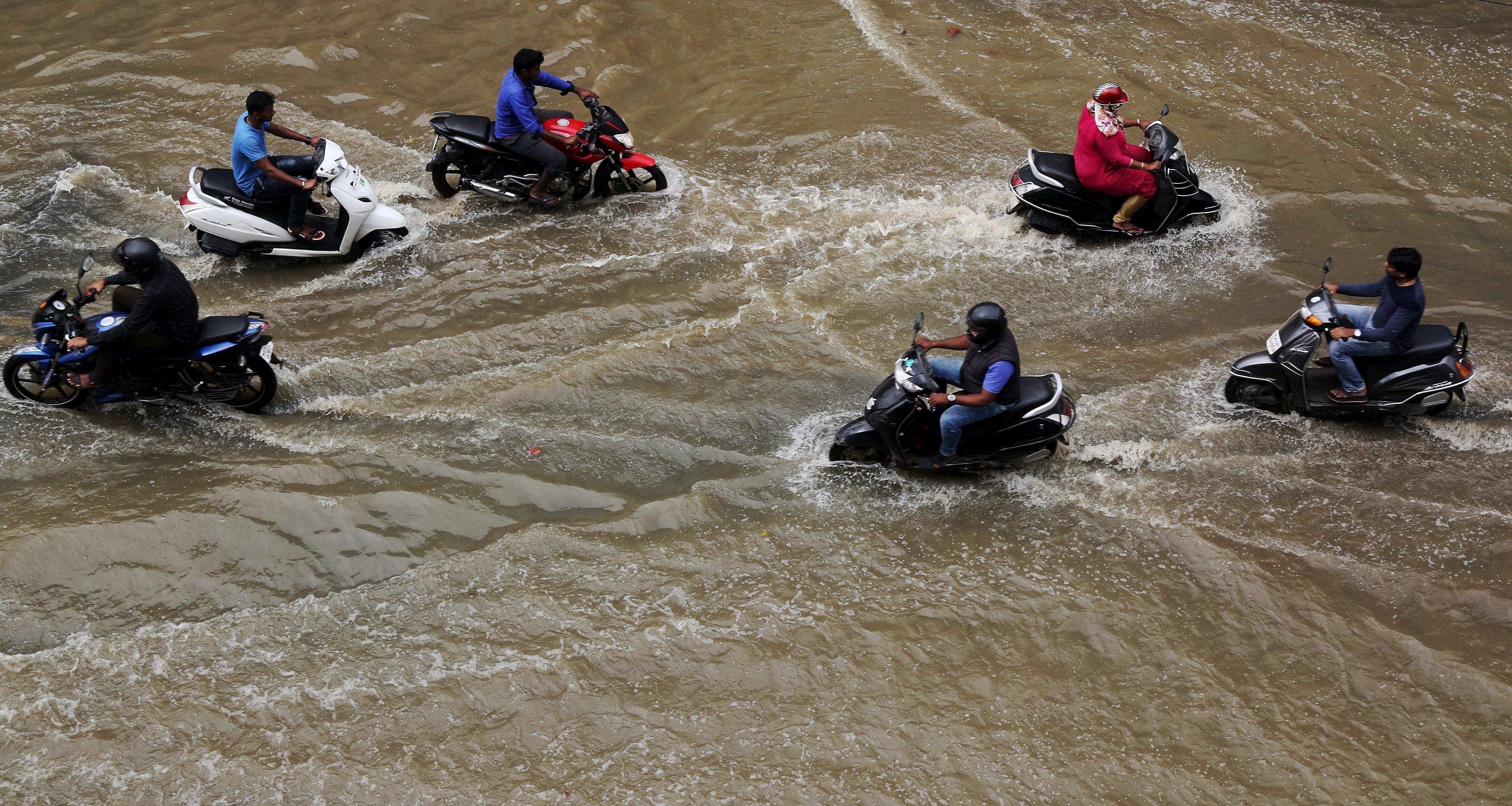Motoristes circulen per un carrer inundat després de les fortes pluges registrades a Bangalore, Índia. /JAGADEESH NV