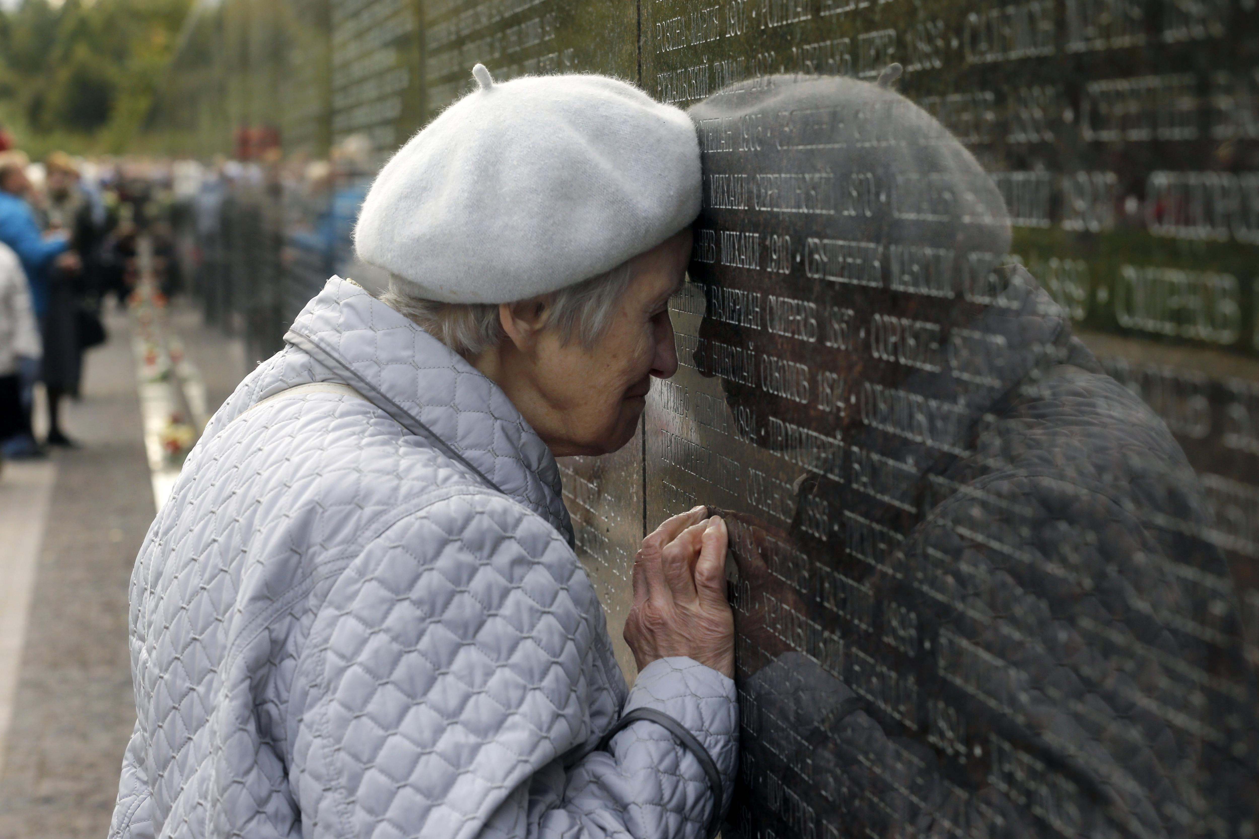 Una dona russa acaricia el nom del seu avi en un monument commemoratiu en el camp de tir de Bútovo, a Moscou, Rússia. /SERGEI CHIRIKOV