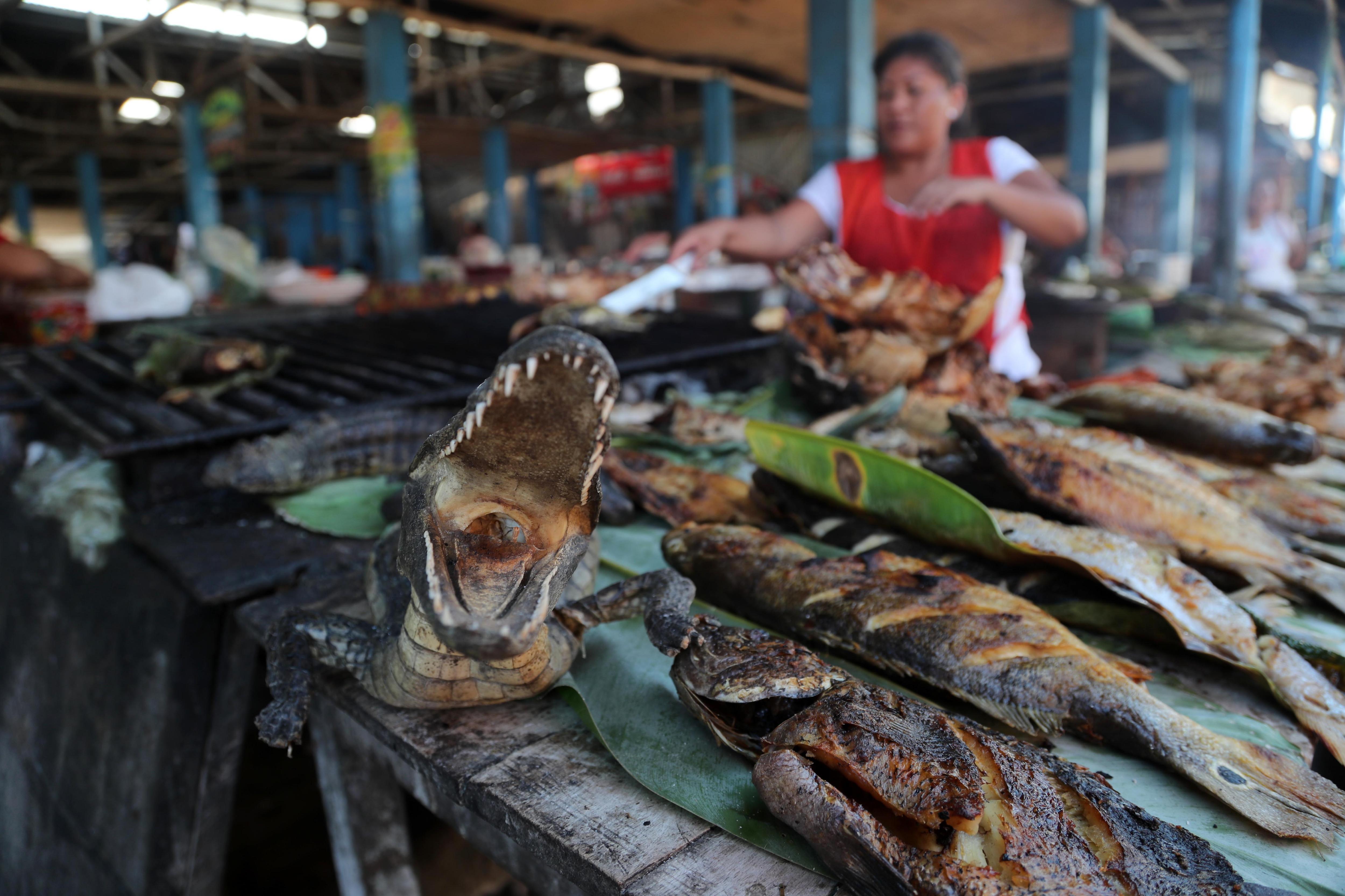 Un venedor ofereix carn de llangardaix en un mercat de Perú. /ERNESTO ARIAS