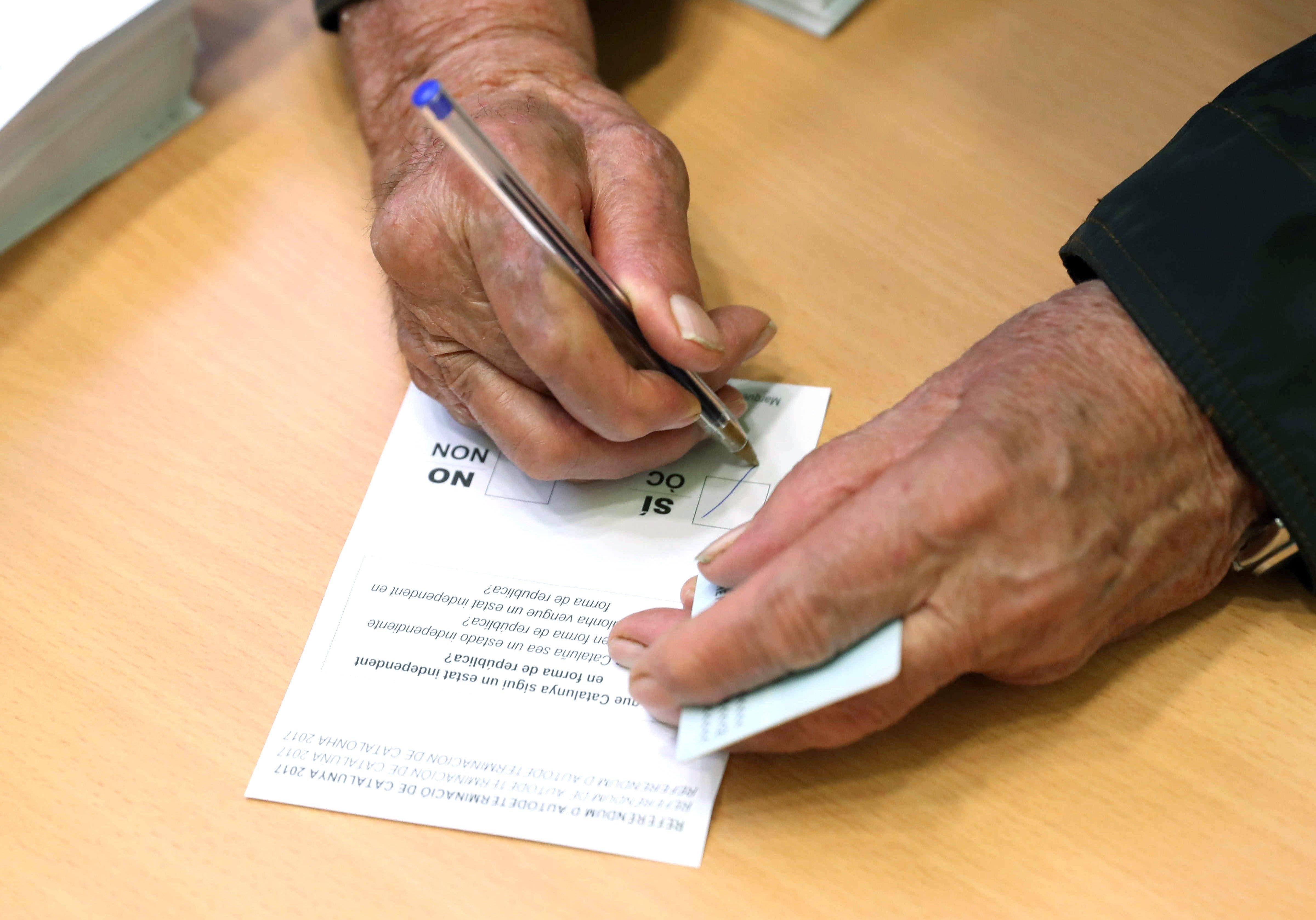 Un ciutadà emplena la papereta per votar en el referèndum independentista al col·legi electoral de l'Escola Jaume I al barri de Sants de Barcelona. /TONI ALBIR