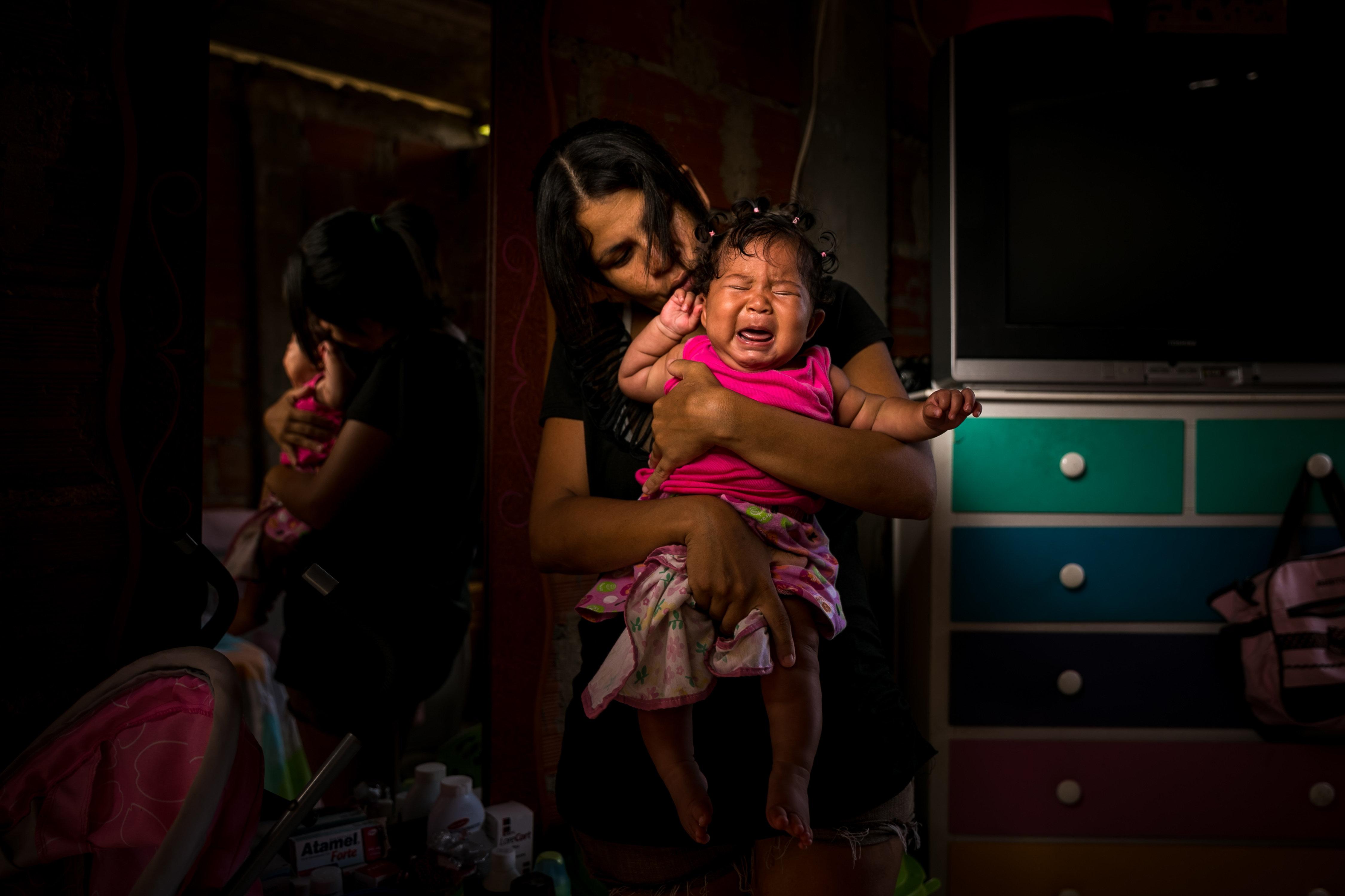 Una mare que pateix malària aguanta la seva filla, que pateix ceguera parcial. El repunt d'almenys tres malalties infeccioses i víriques a Veneçuela ha deixat veure el debilitament del seu sistema sanitari. /MIGUEL GUTIÉRREZ