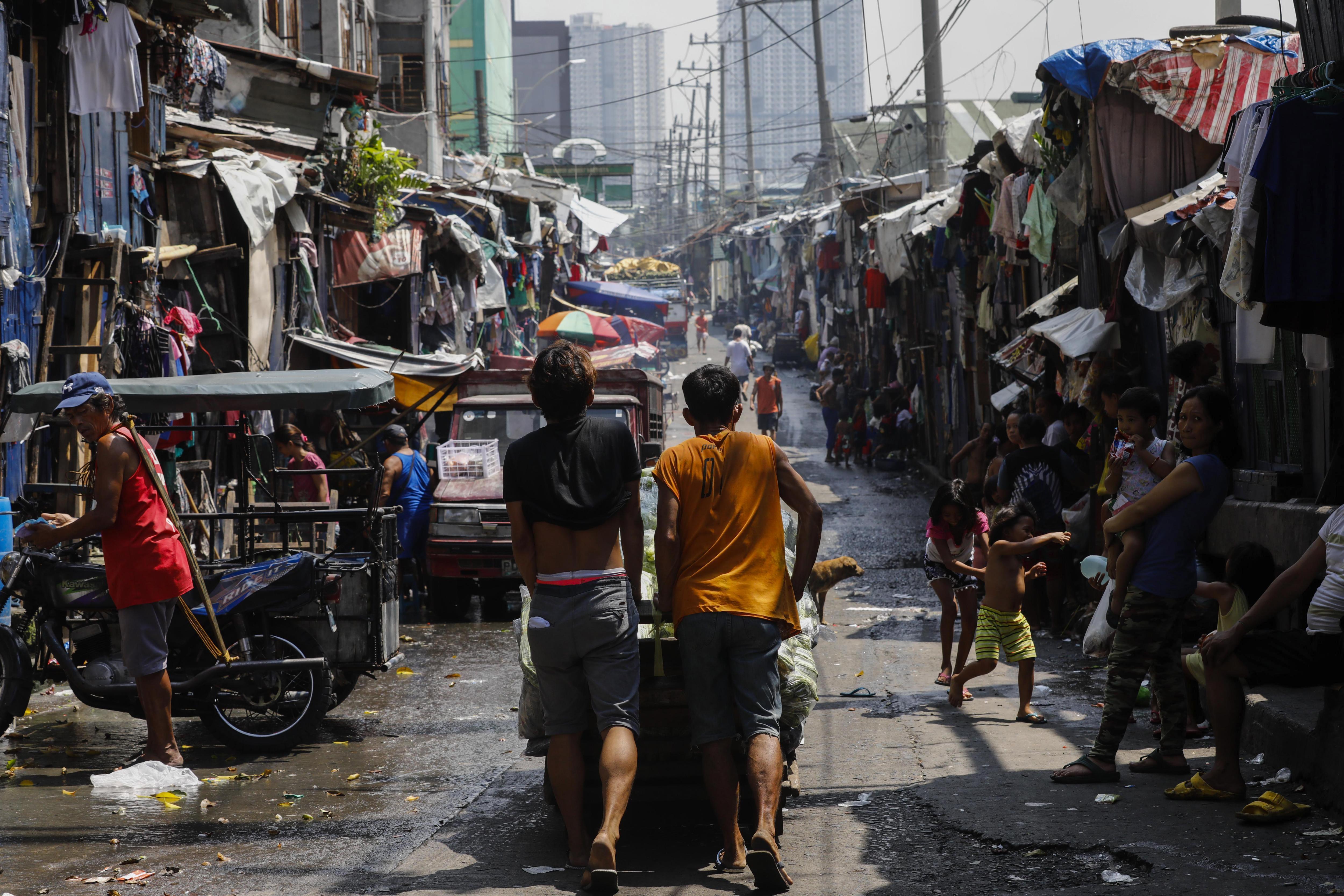 Dos venedors empenyen un carret ple de verdures per vendre-les en un mercat de fruites a Quezon, Manila (Filipines). /ROLEX DELA PENA