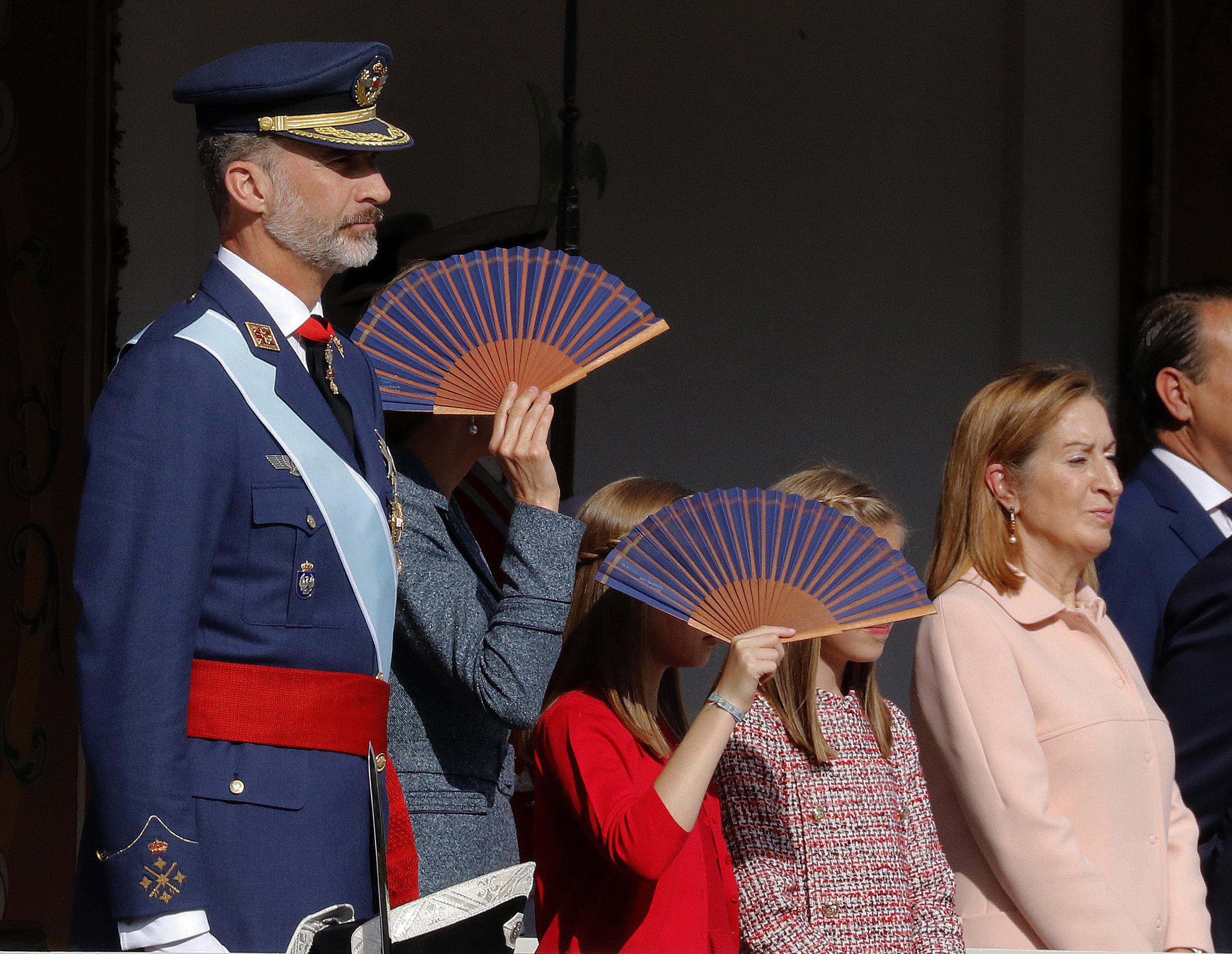 La reina Letícia i les seves filles, la princesa Elionor i la infanta Sofia, es protegeixen del sol amb uns ventalls, al costat del Rei Felip VI, i la presidenta del Congrés, Ana Pastor, durant la desfilada del Dia de la Festa Nacional./Víctor Lerena