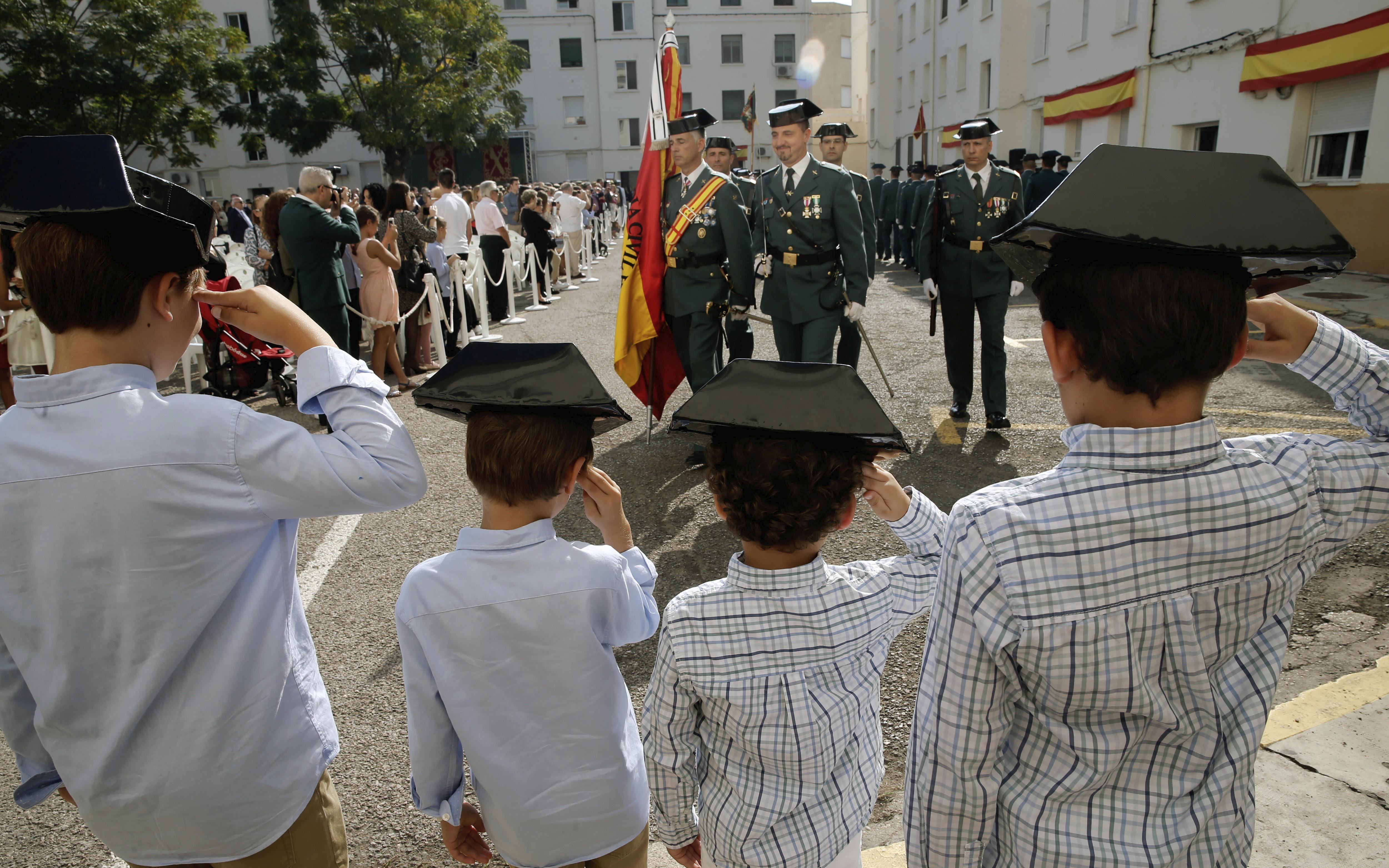 Quatre nens saluden el pas dels guàrdies civils a la Comandància de València durant els actes de la Verge del Pilar, patrona del cos./Juan Carlos Cárdenas