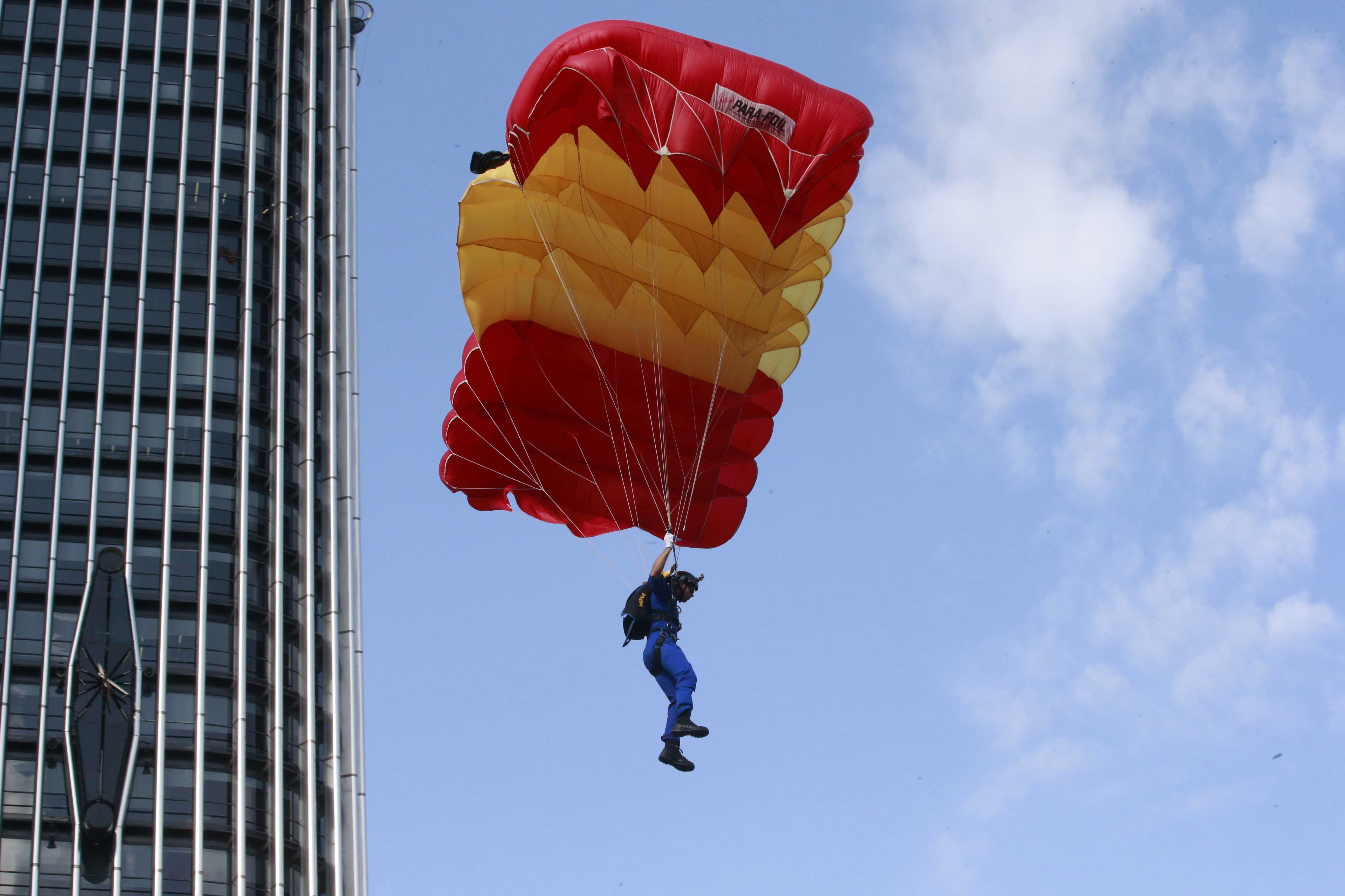 Un paracaigudista descendeix fins a l'asfalt del Passeig de la Castellana a l'inici de la desfilada del Dia de la Festa Nacional./Zipi