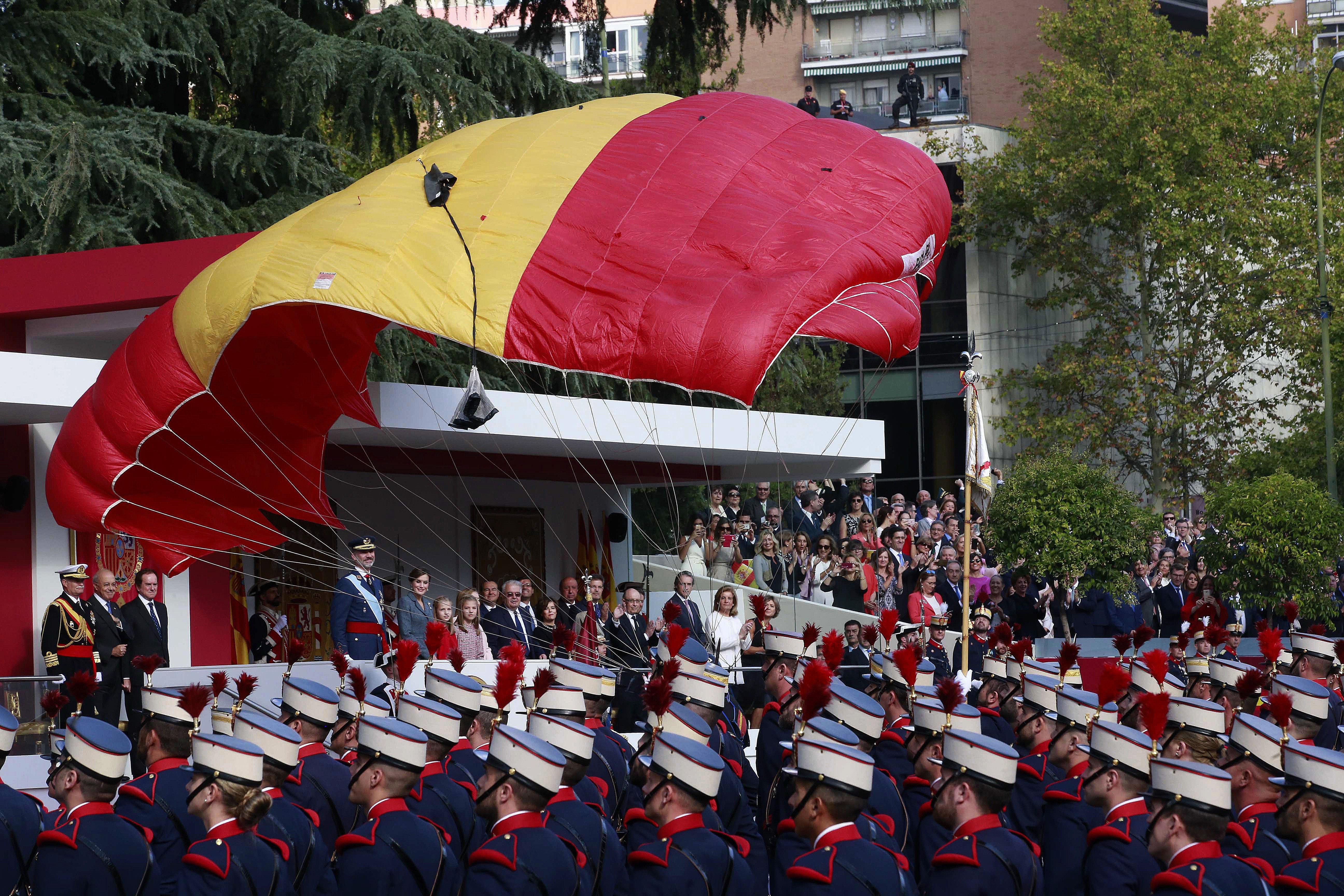 Un integrant de la Patrulla Acrobàtica de Paracaigudisme de l'Exèrcit de l'Aire descendeix fins a l'asfalt del Passeig de la Castellana a l'inici de la desfilada del Dia de la Festa Nacional./Zipi