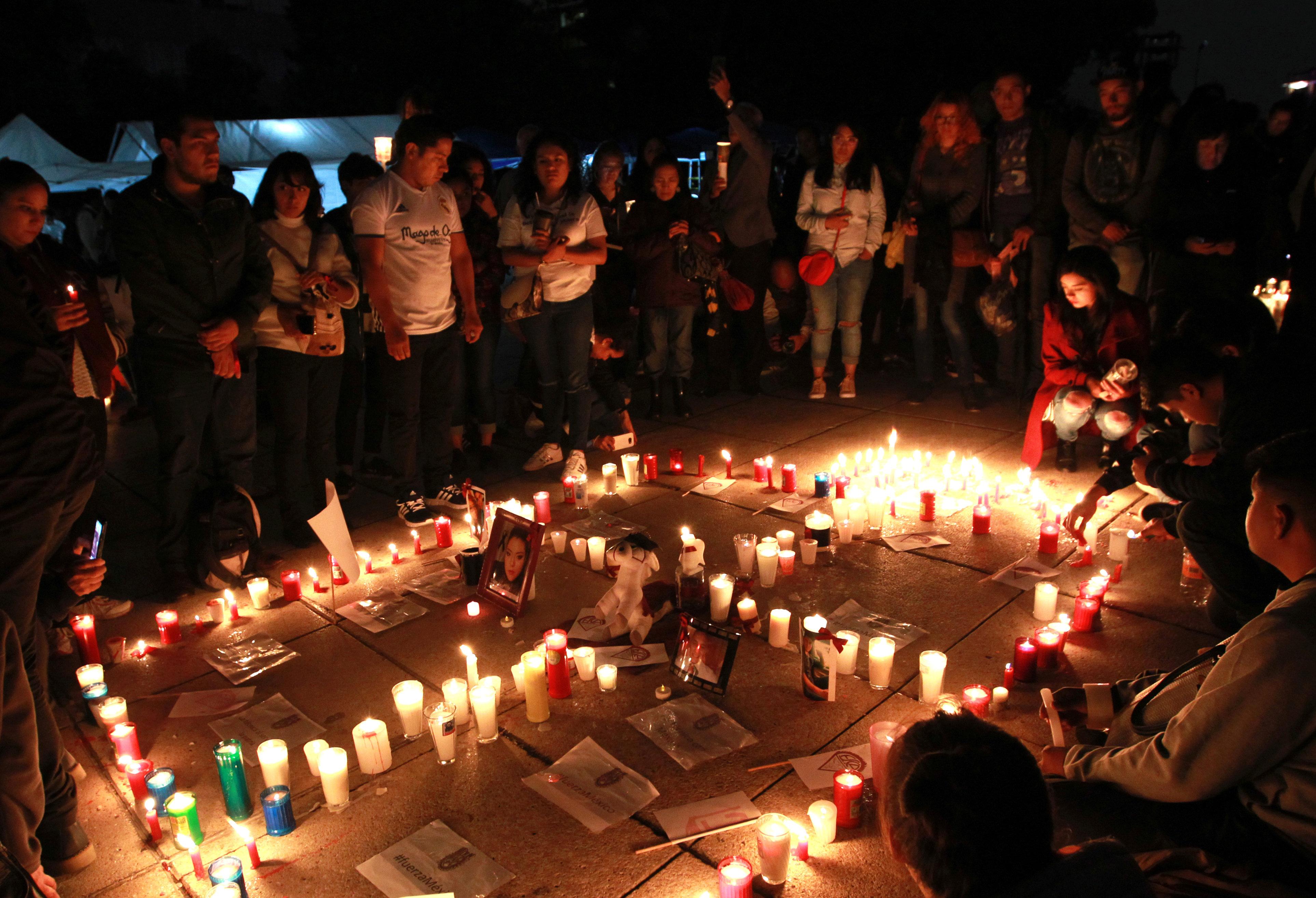 Familiars i amics de víctimes mortals dels terratrèmols de setembre porten espelmes enceses, flors i fotografies en suport i solidaritat, al Monument a la Revolució, a la Ciutat de Mèxic./Mario Guzmán