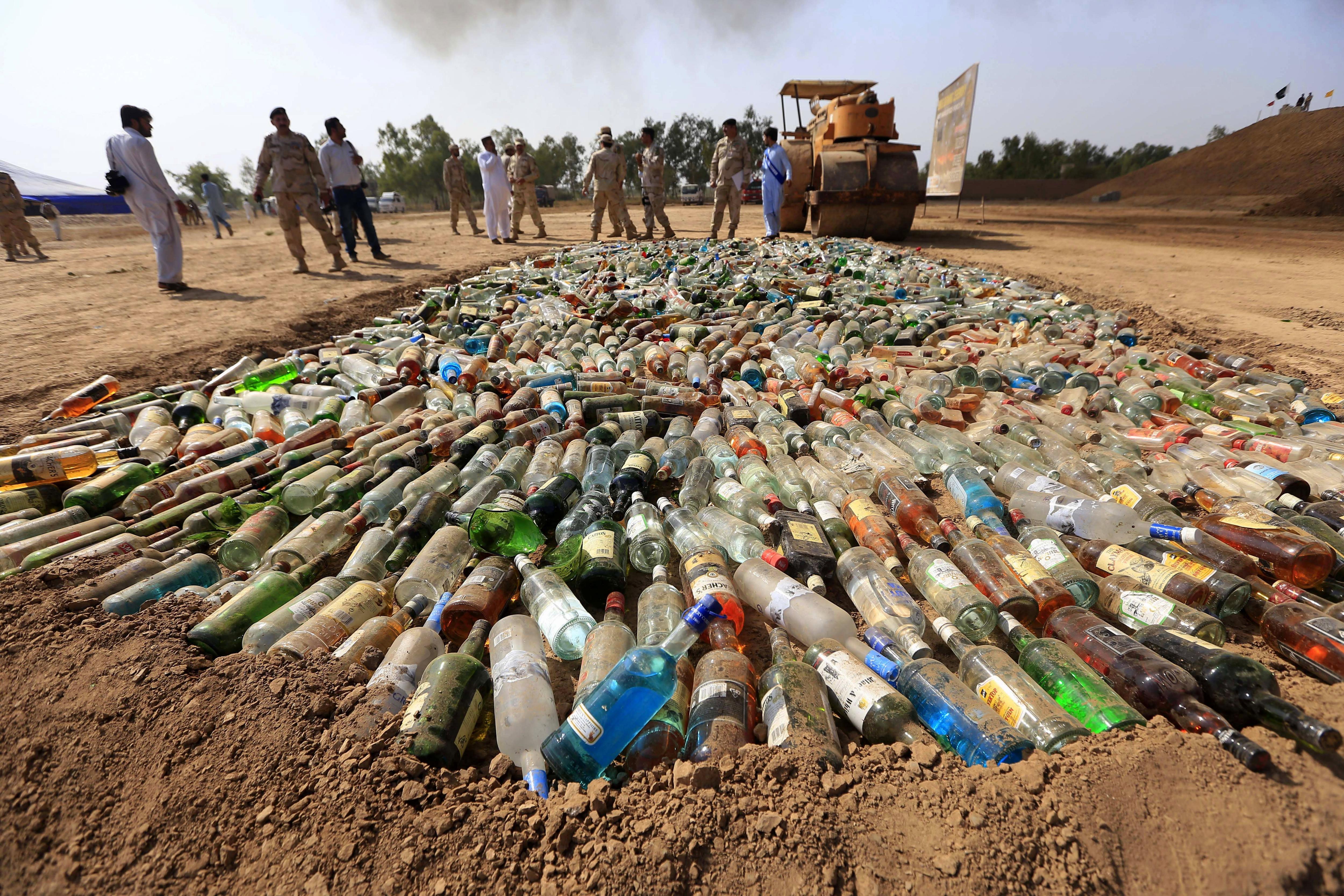 Oficials de les Forces Anti-Narcòtics (ANF) munten guàrdia durant una crema d'alcohol de contraban a Peshawar, al Pakistan. Les autoritats pakistaneses van cremar tones d'haixix, heroïna, cigarrets i licors de contraban que havien estat confiscats./ARSHAD ARBAB