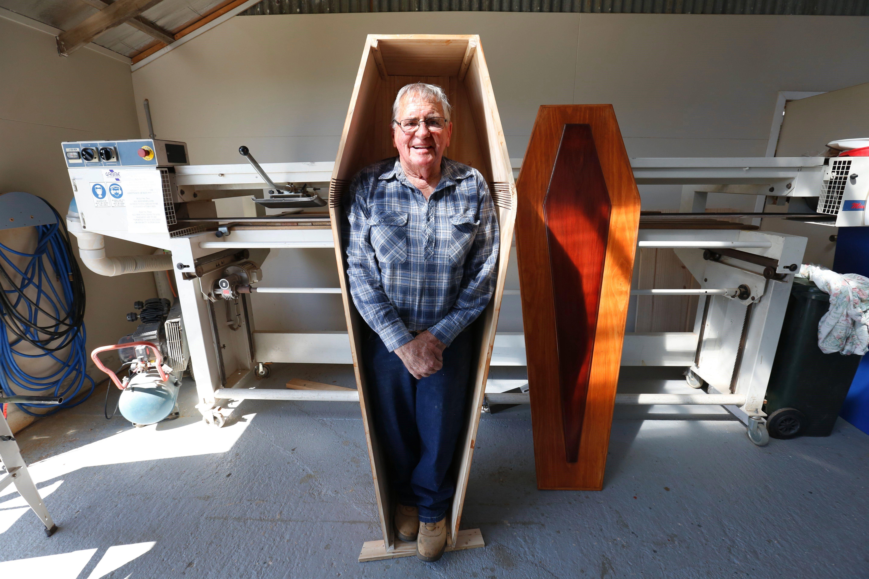 Russel Game posa al seu fèretre, construït per ell mateix, al taller on ajuda a diverses persones a construir el seu propi taüt al Club del Taüt a Ulverstone, al nord de Tasmània, a Austràlia. El taüt estarà proveït de prestatgeries per poder ser usat com a moble de magatzematge a la seva casa fins que sigui necessitat./Barbara Walton