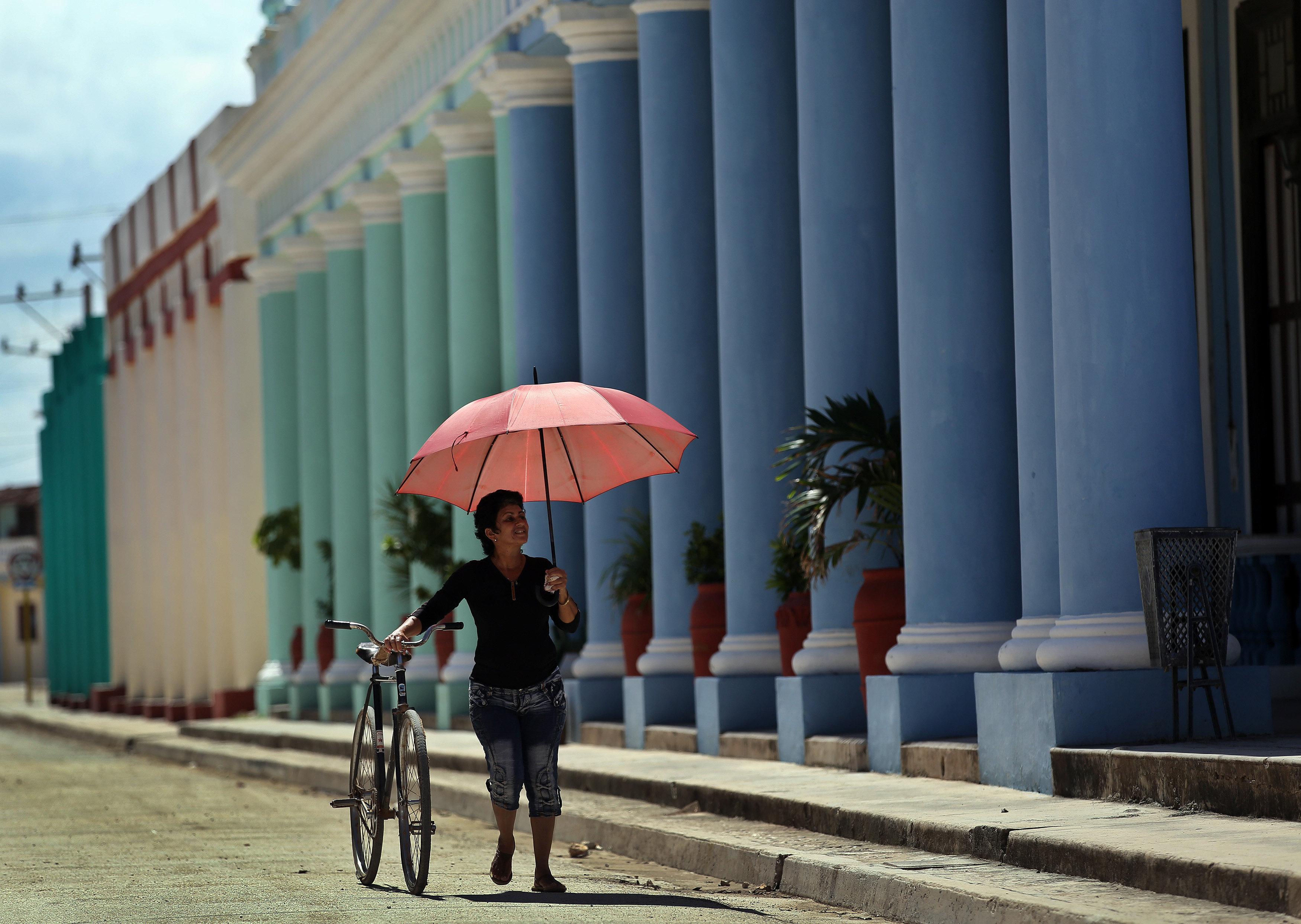Una dona es cobreix del sol amb un paraigua a Cuba. /ALEJANDRO ERNESTO