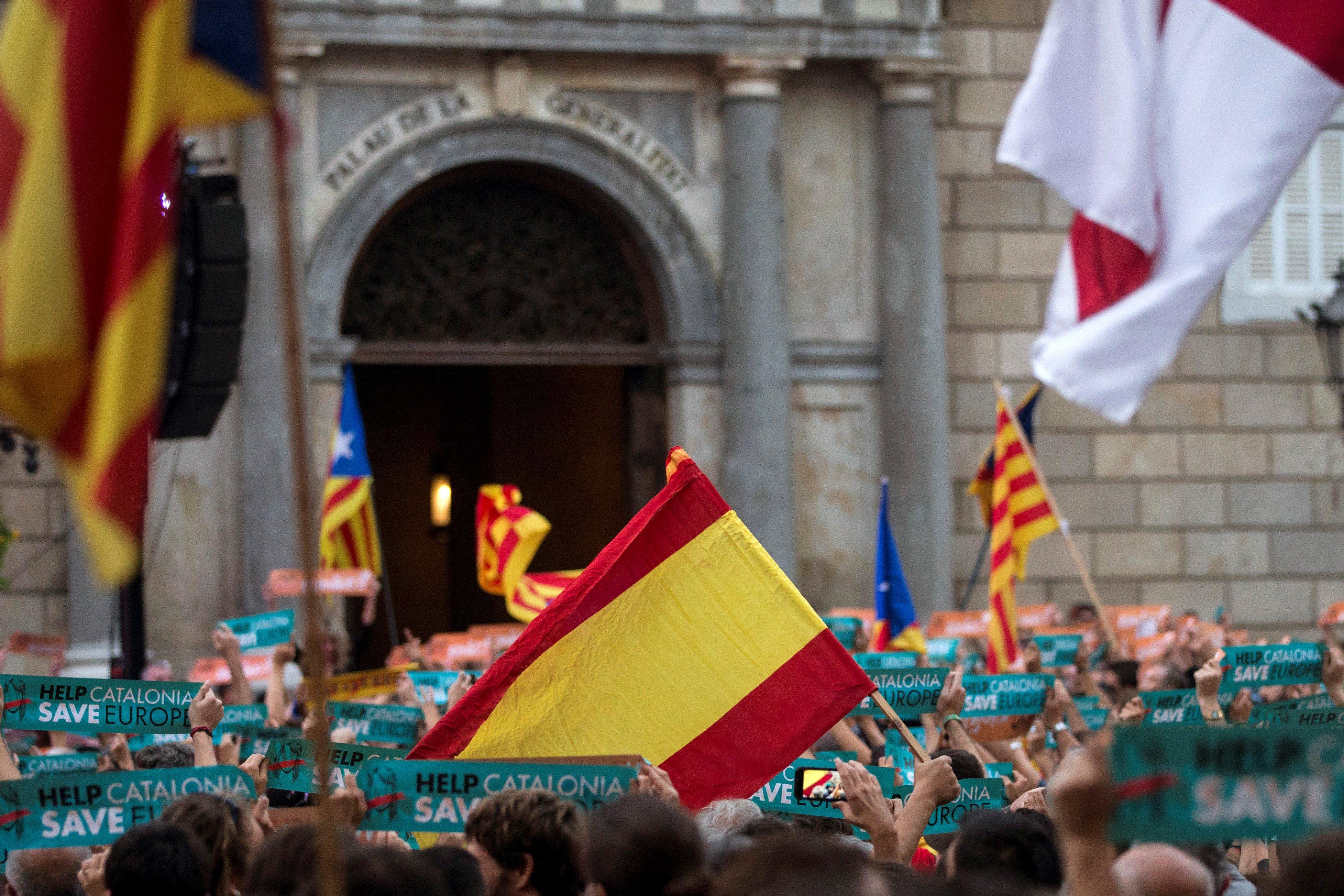 Una bandera espanyola es barreja amb altres independentistes a la plaça Sant Jaume de Barcelona. /EFE