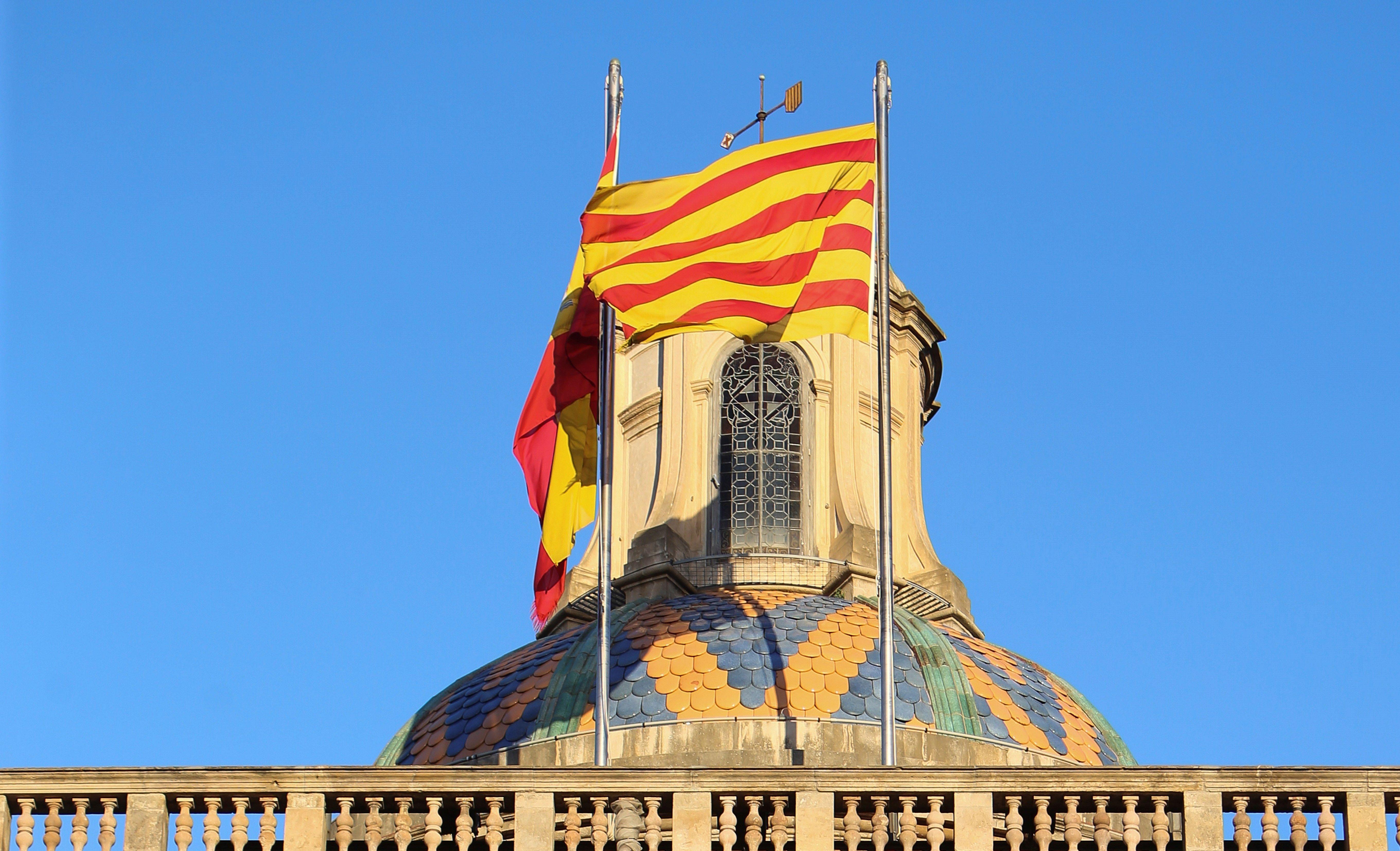 La senyera i la bandera d'Espanya onegen en el Palau de la Generalitat. /EFE