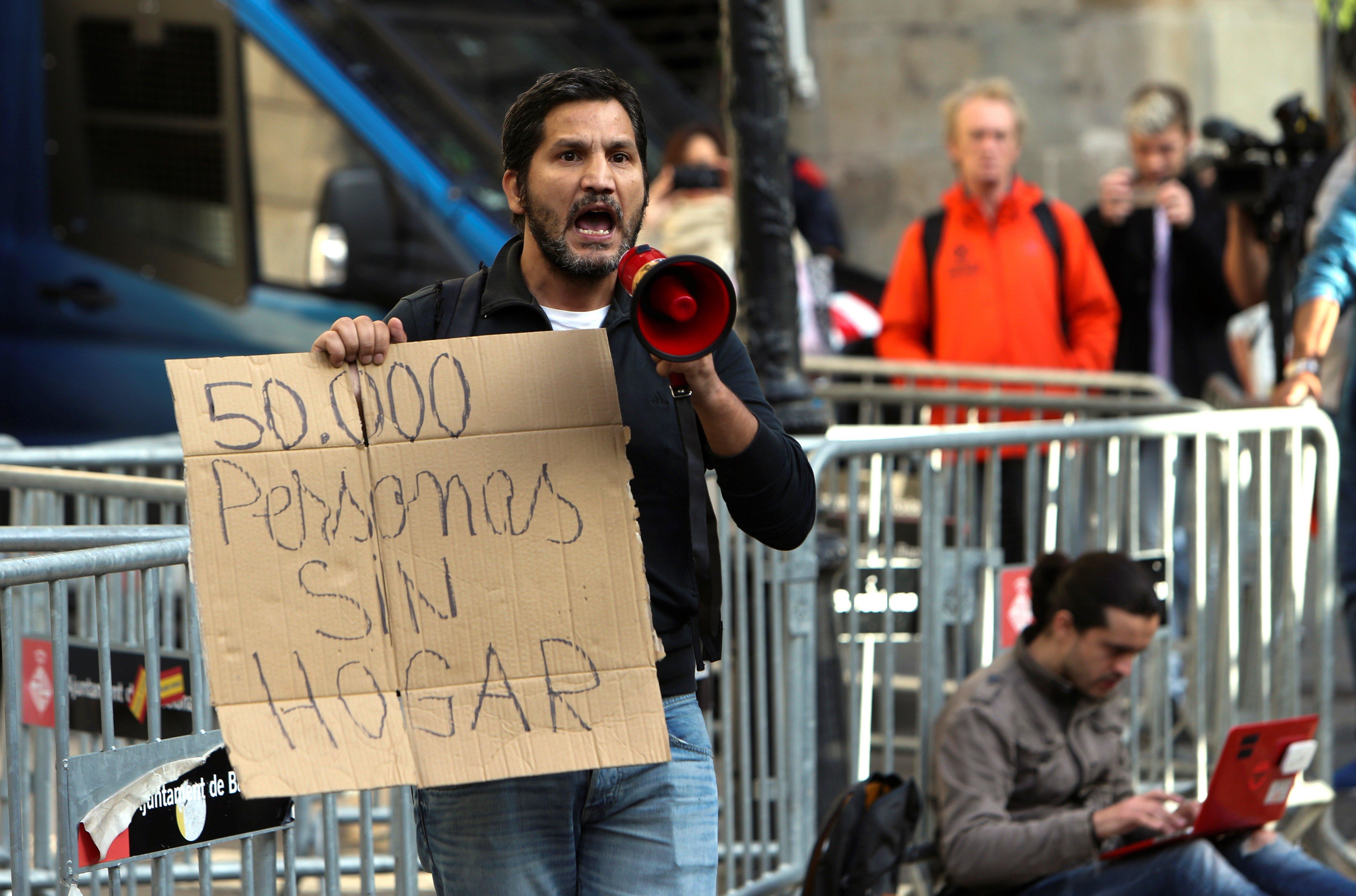 """Una persona mostra un cartell amb un text que diu """"50.000 persones sense llar"""" a la plaça Sant Jaume. /JAVIER ETXEZARRETA"""