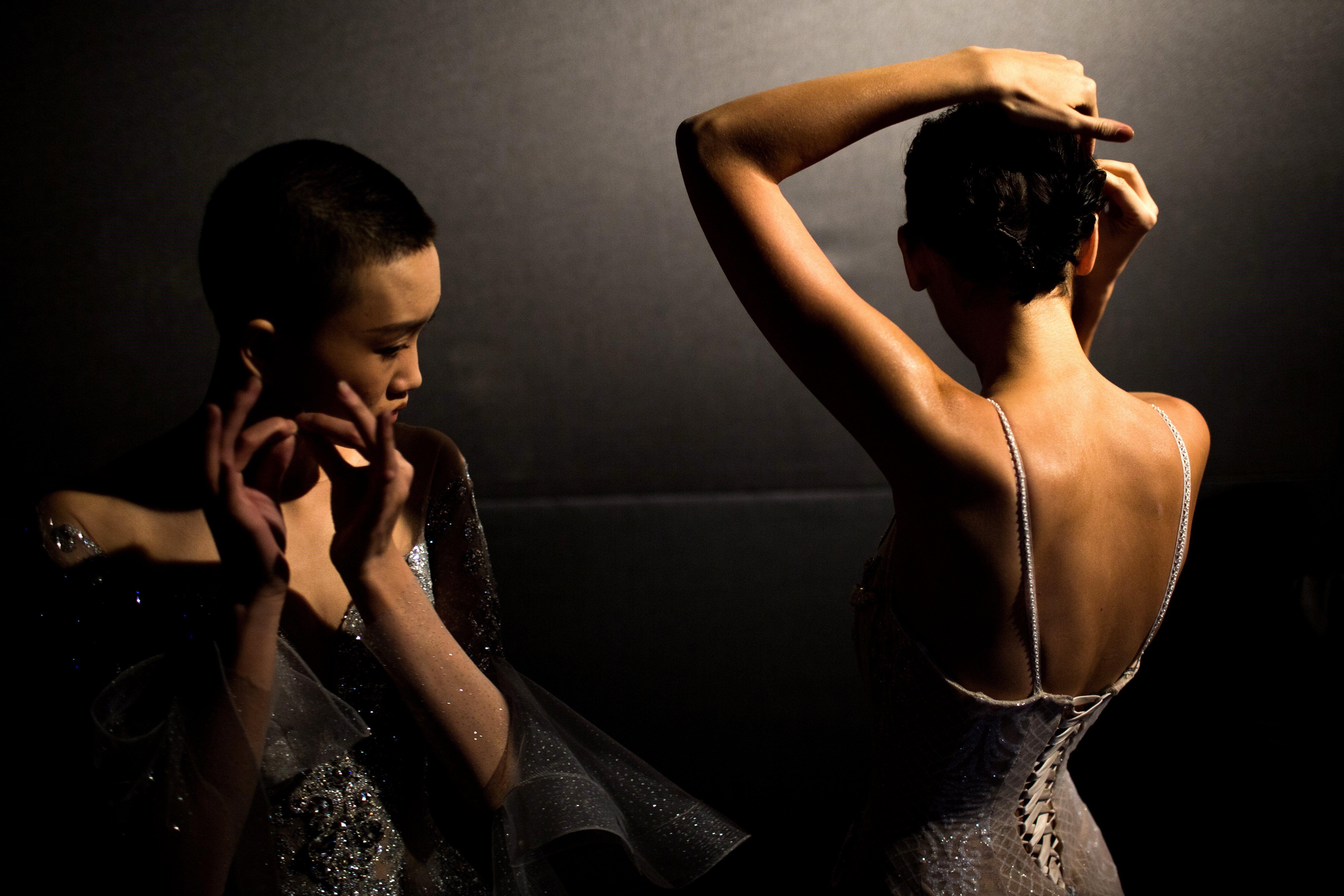 """Dos models es preparen abans de la presentació de la col·lecció nupcial """"Jusere"""", obra de la dissenyadora xinesa Yu Aiping, durant la Setmana de la Moda de Pequín (Xina). /ROMAN PILIPEY"""