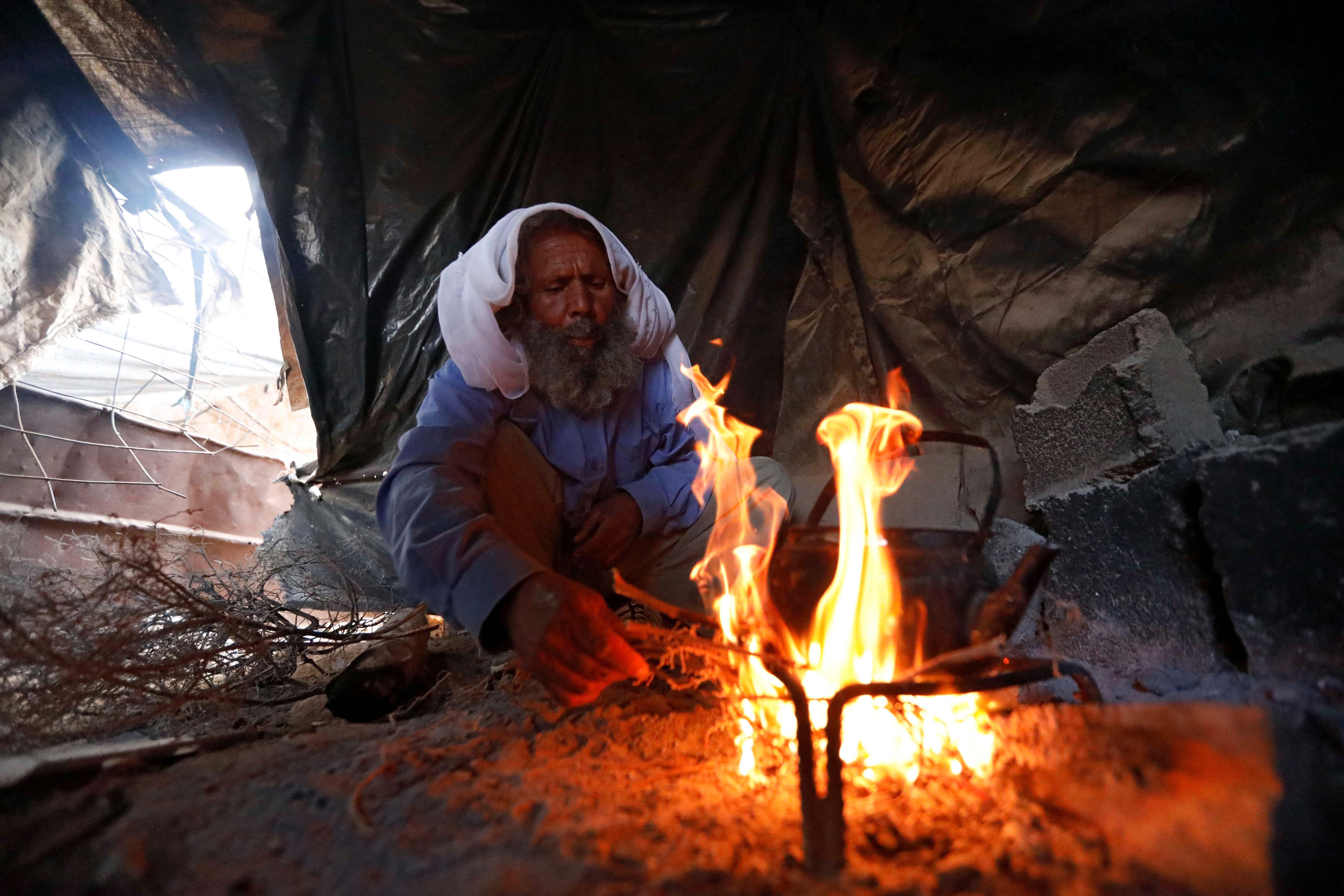 Un home palestí prepara una beguda calenta sobre les flames d'una foguera en una cova, que empra de llar, en un poblat prop de la ciutat de Yatta, al sud d'Hebron, Palestina. /ABED AL HASHLAMOUN