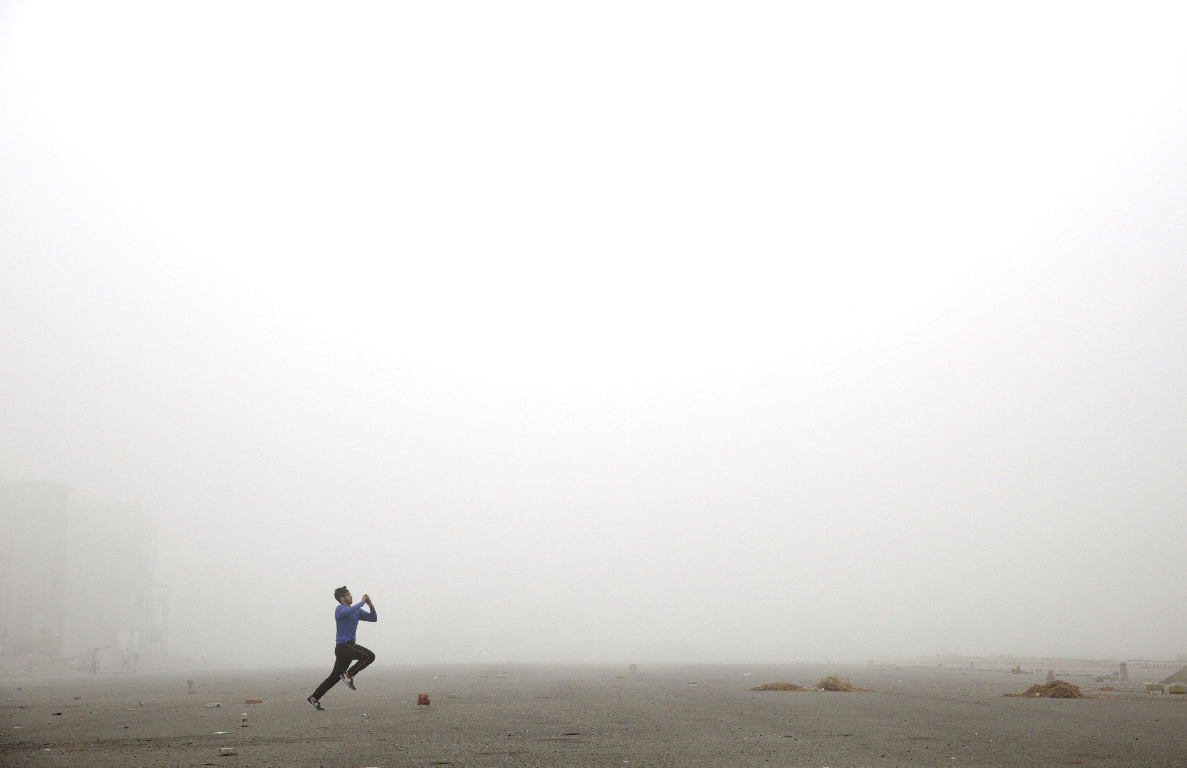 Un home juga al criquet en un dia ennuvolat, que es mantindrà diversos dies després de baixades de temperatura, a Amristar (Índia). /RAMINDER PAL SINGH