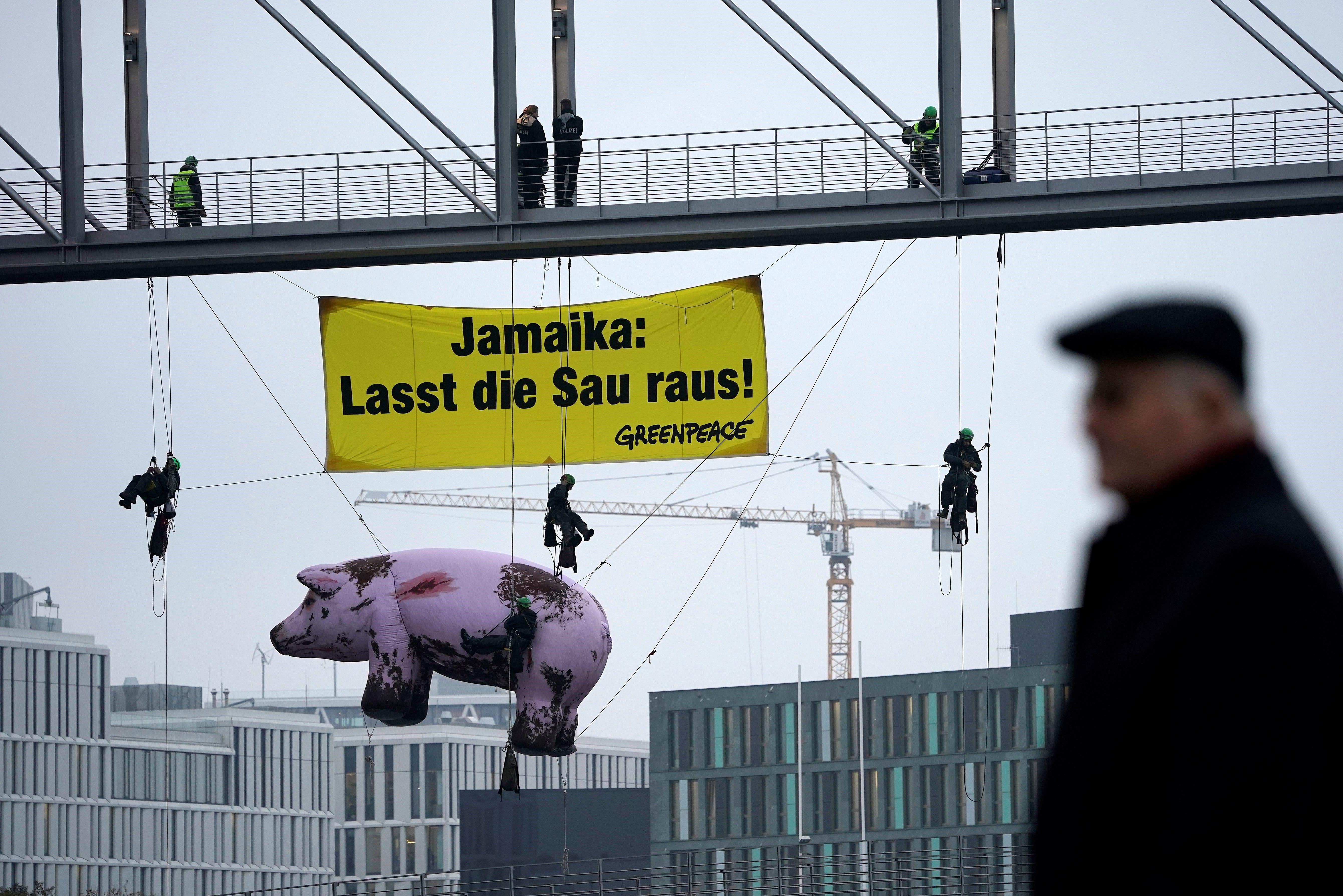 Activistes de Greenpeace pengen un cartell i el ninot d'un porc contra la cria intensiva prop d'on se celebra una nova ronda de converses per a la formació de govern a Berlín (Alemanya) . /FELIPE TRUEBA