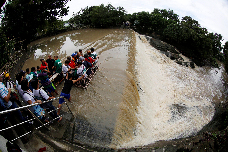 Diverses persones creuen una presa inundada a Filipines, abans de la celebració del Cim de l'Associació de Nacions del Sud-est Asiàtic 2017. /FRANCIS R. MALASIG