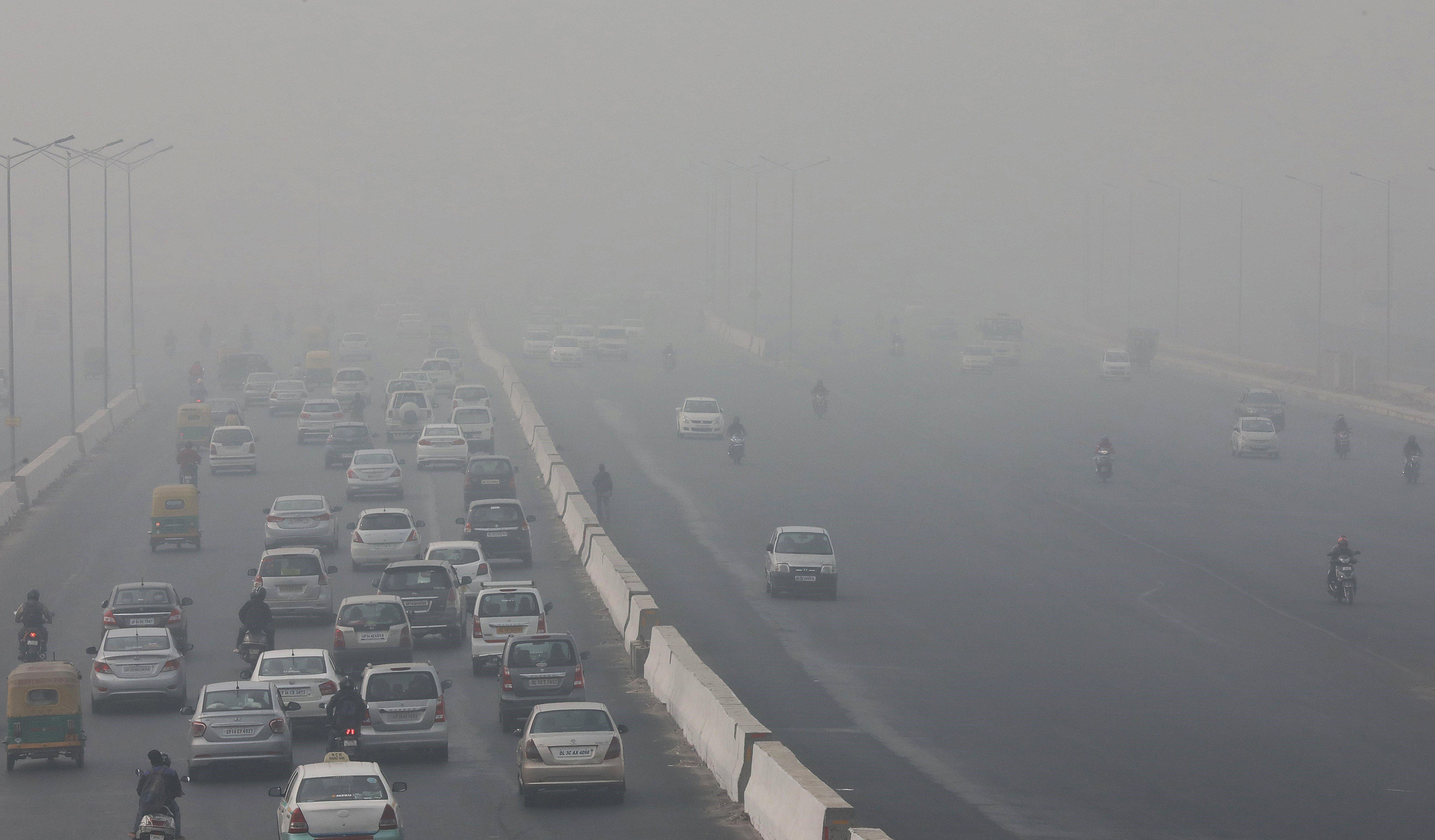 Diversos vehicles circulen enmig de la boira a Nova Delhi (Índia). Els ciutadans de la capital s'enfronten des de fa dies a alts nivells de contaminació. /HARISH TYAGI