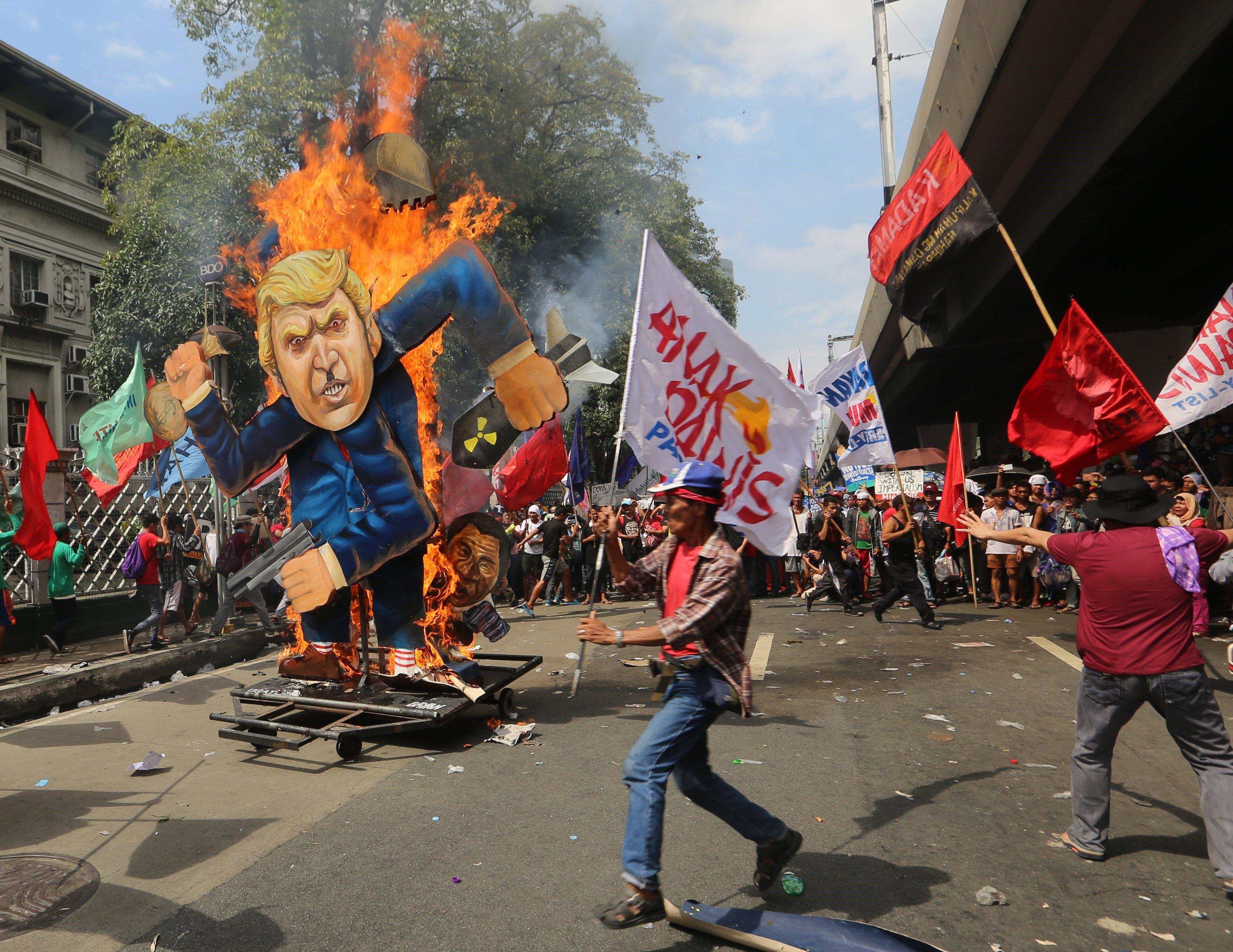 Manifestants filipins cremen una figura que representa el president dels EUA, Donald Trump, durant una protesta en el marc de la celebració del Cim de l'Associació de Nacions del Sud-est Asiàtic (ASEAN), a Manila, Filipines. /KENJI HASEGAWA