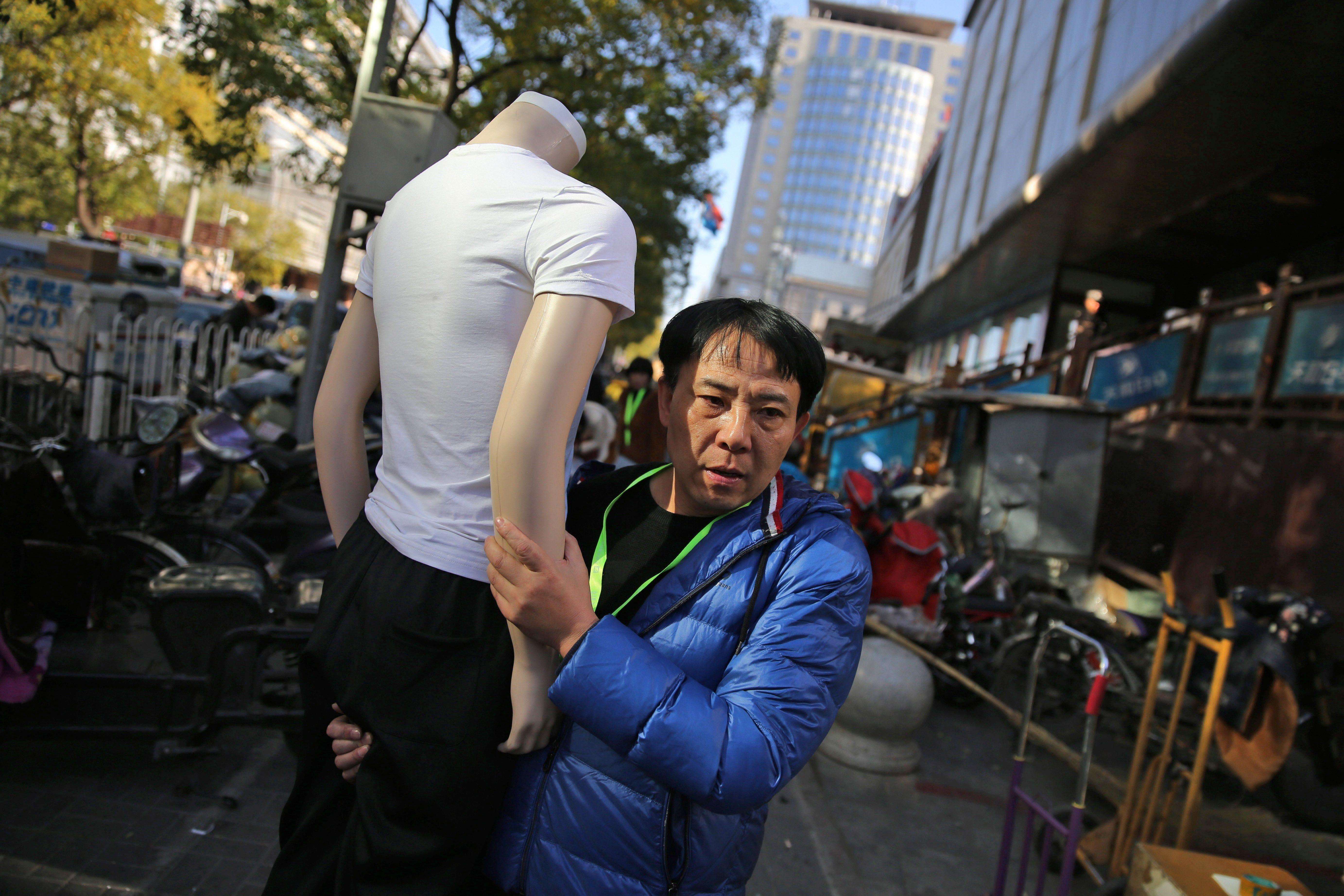 Un venedor xinès transporta la seva mercaderia davant un mercat de venda a l'engròs que roman tancat a causa de la nova política de planificació urbana de Pequín, Xina. /WU HONG