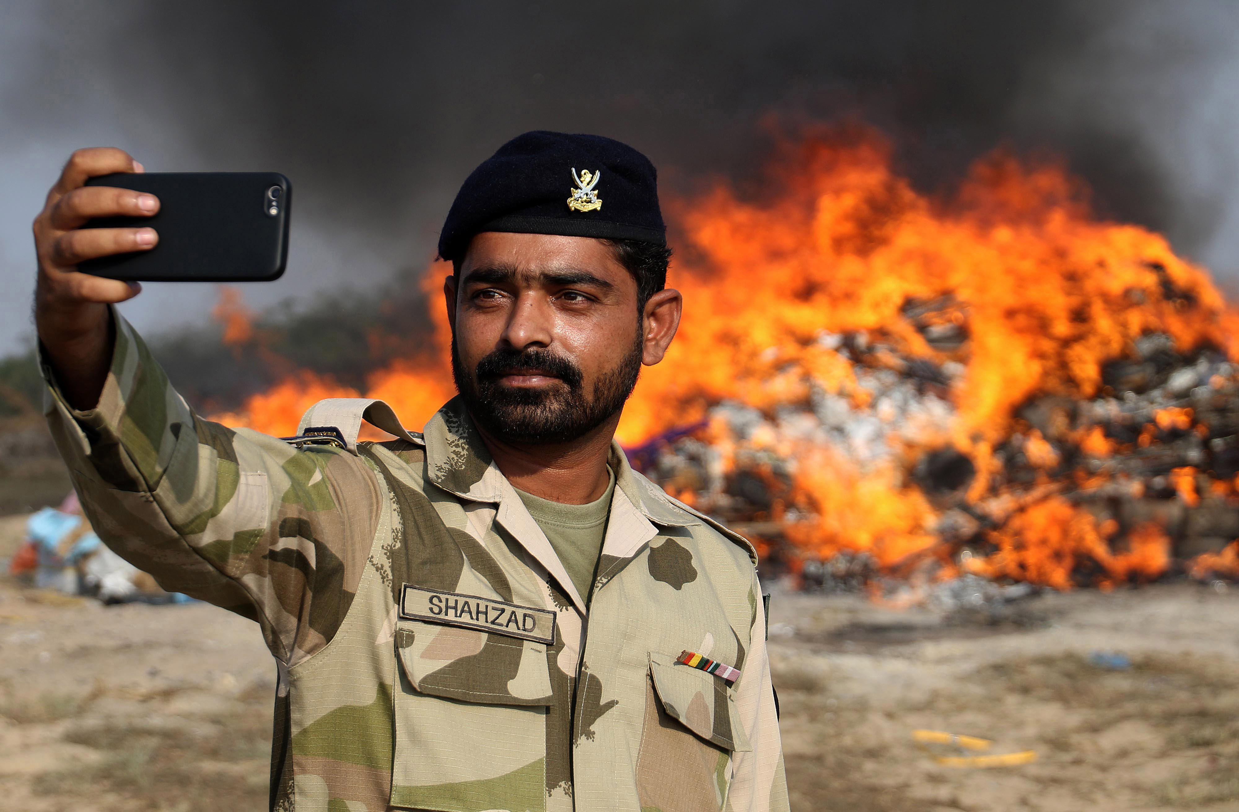 Un guàrdia costaner pakistanès es fa una foto mentre es crema licor il·legal a Karachi (Pakistan). /SHAHZAIB AKBER