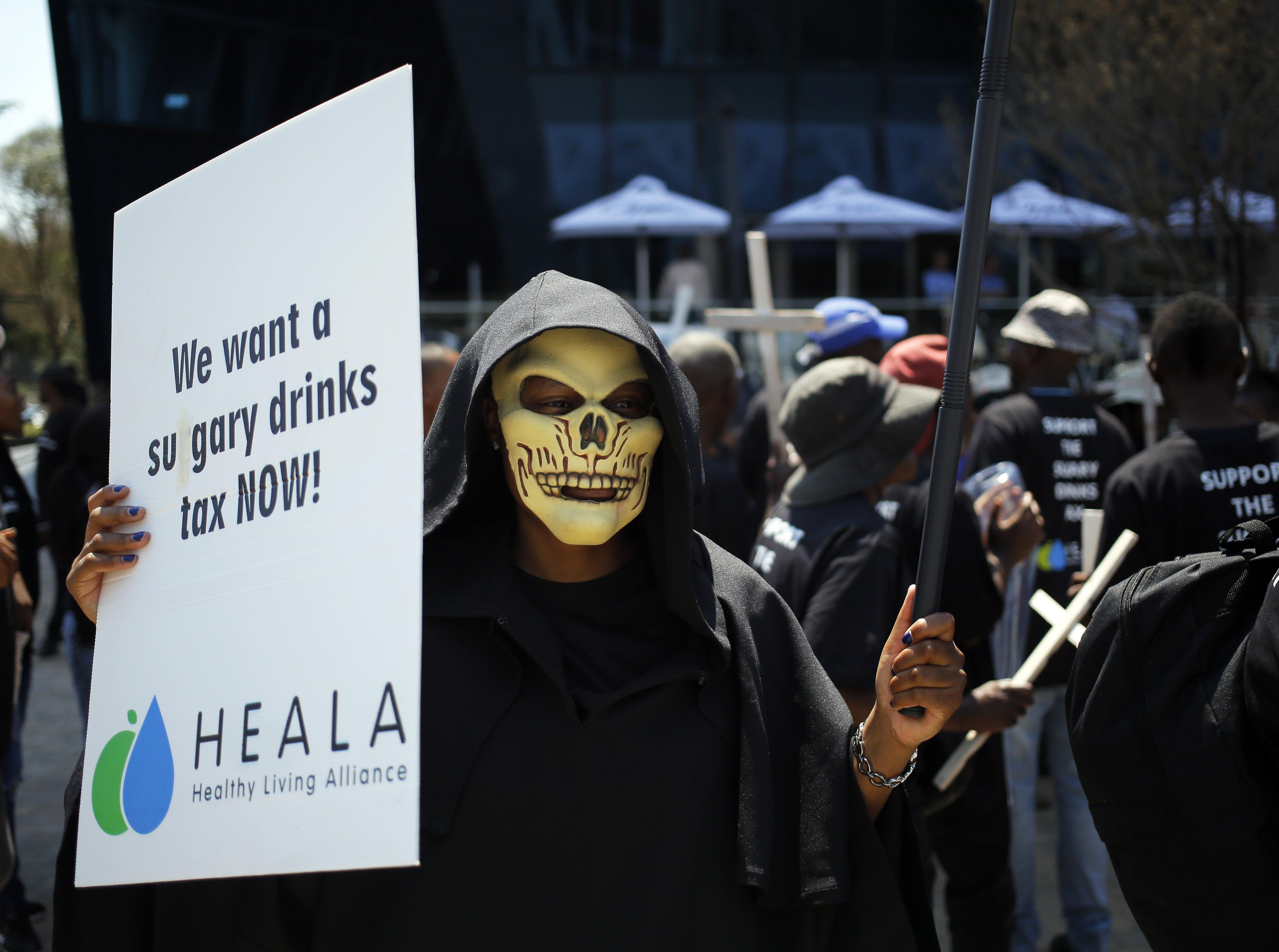 Diversos manifestants participen en una protesta en el marc de la celebració del Dia Mundial de la Diabetis a l'exterior de les oficines de Coca-Cola a Johannesburg (Sud-àfrica). /KIM LUDBROOK