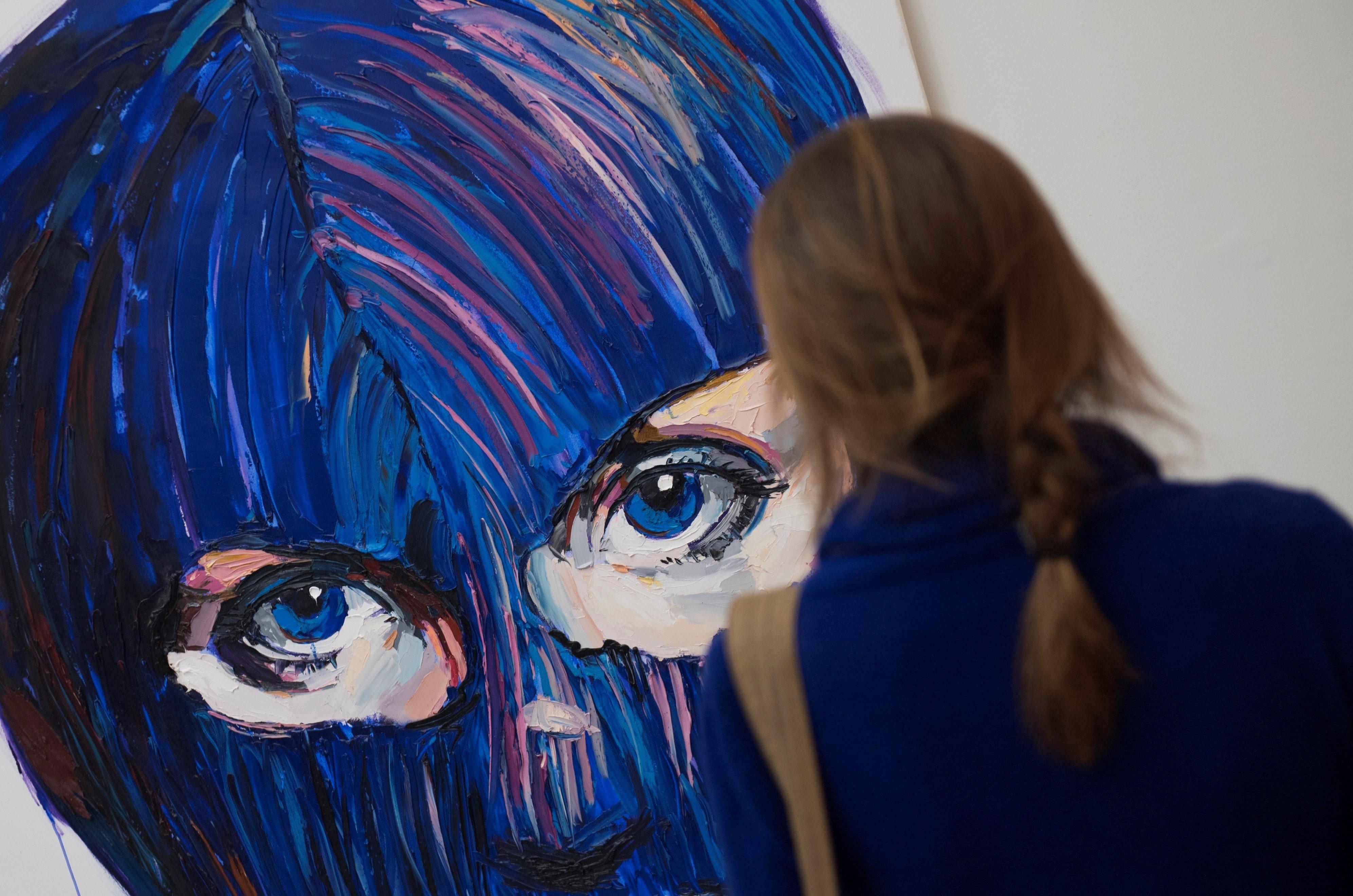 """Una visitant passa al costat d'una obra que representa el grup rus de punk feminista Pussy Riot a l'exposició """"Art Riot: Activisme postsoviètic"""" a la galeria Saatchi del centre de Londres (Regne Unit). /WILL OLIVER"""
