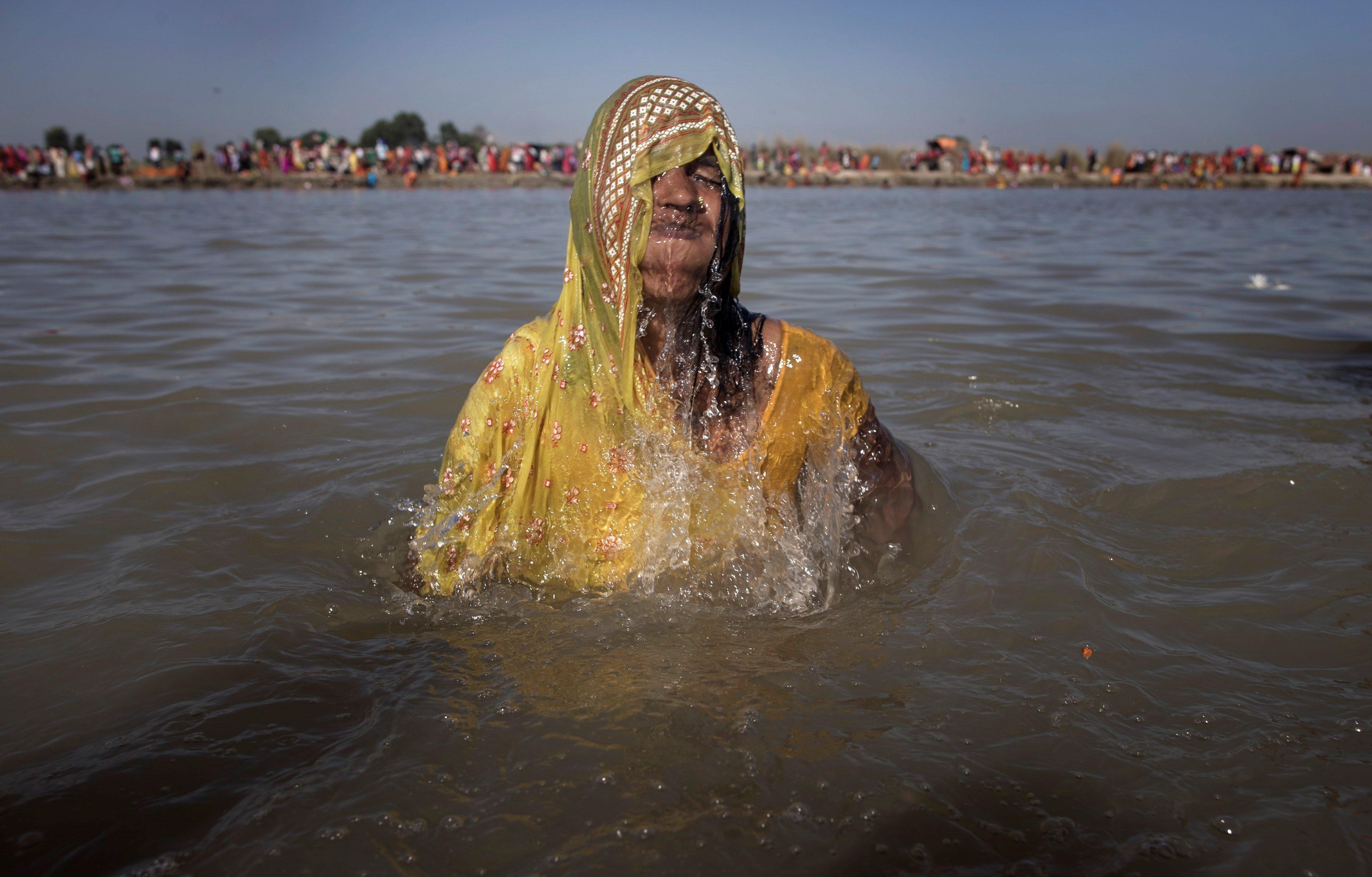 """Marani Devi Chaudhary, de 40 anys i que creu estar posseïda per un esperit maligne, es pren un bany sagrat un dia de lluna plena durant la celebració del """"Festival dels fantasmes"""", al riu Kamala en el districte de Danusha (Nepal). /NARENDRA SHRESTHA"""