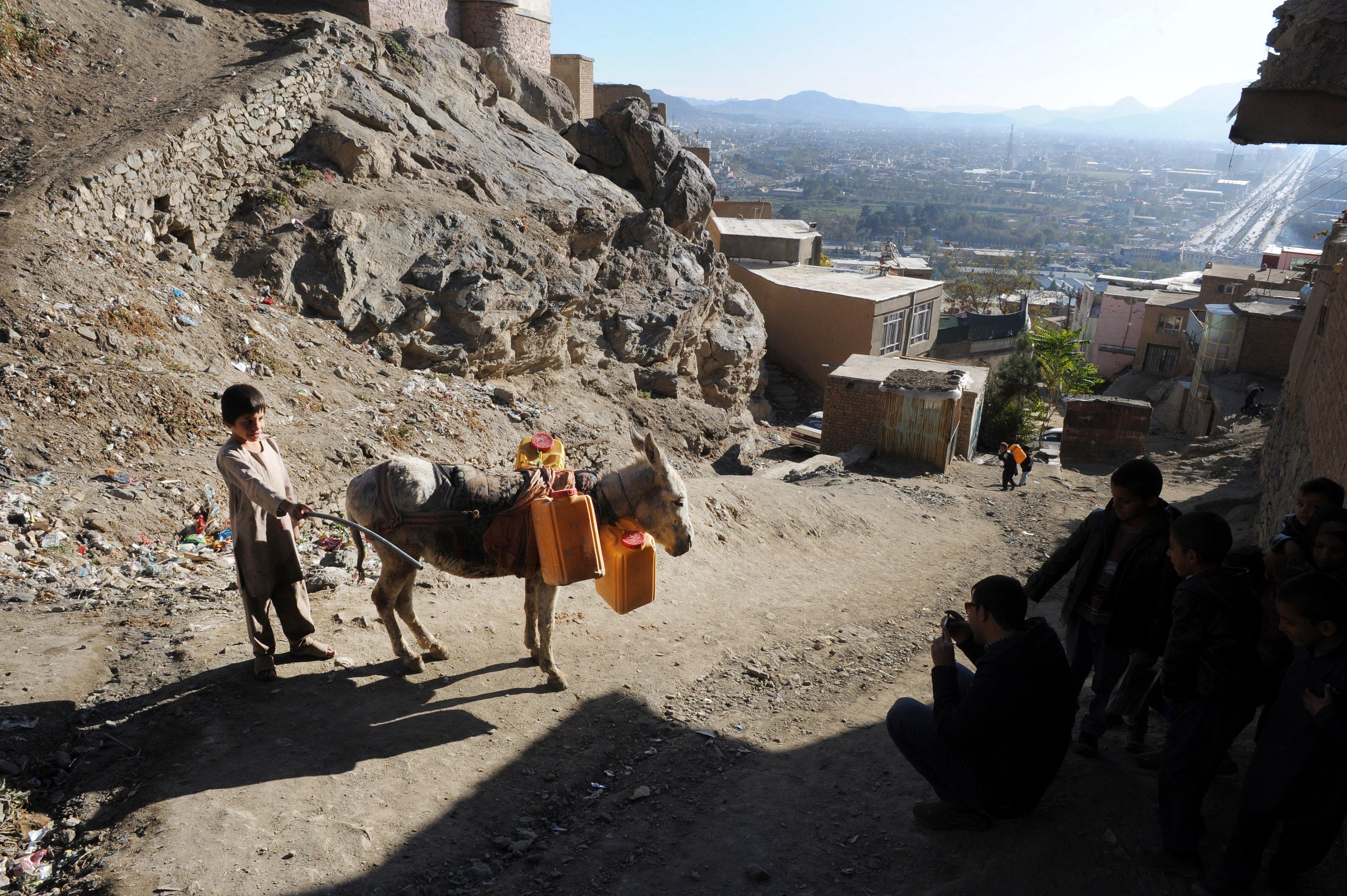 Un nin transporta tancs d'aigua a l'est de Kabul (Afganistan). Almenys el 60% dels habitants de la capital no tenen accés a l'aigua potable. /JAWAD JALALI