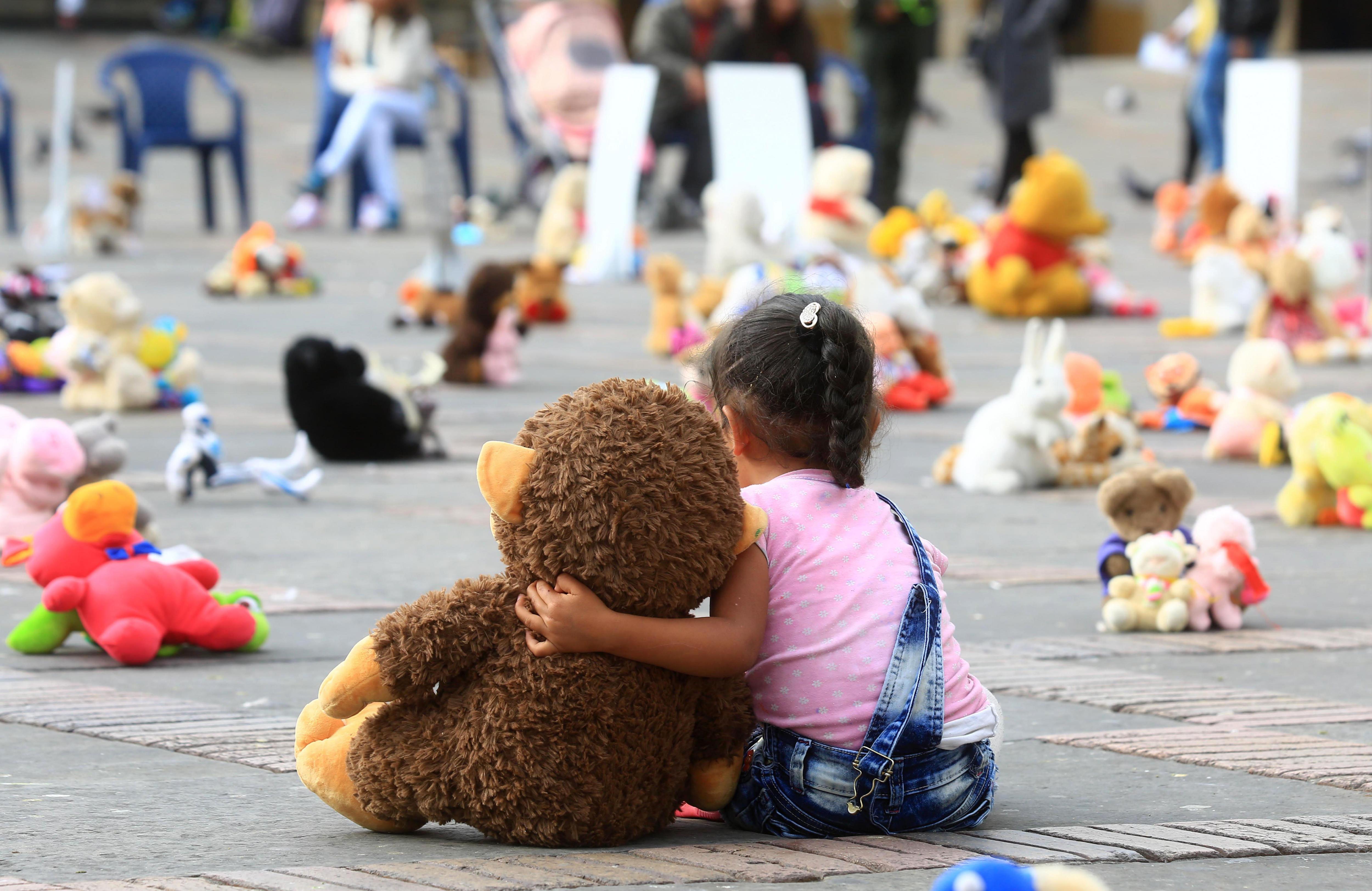 """Una nina abraça un peluix durant un """"plantada de joguines"""" organitzada per Aldeas Infantiles SOS Colombia contra l'abús sexual infantil a Bogotà (Colòmbia). /MAURICIO OSORIO"""