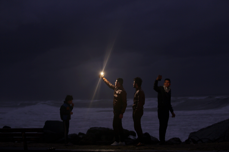 Un grup de joves palestins prenen fotos a la platja durant un dia de tempesta, a Gaza. /MOHAMED SABER