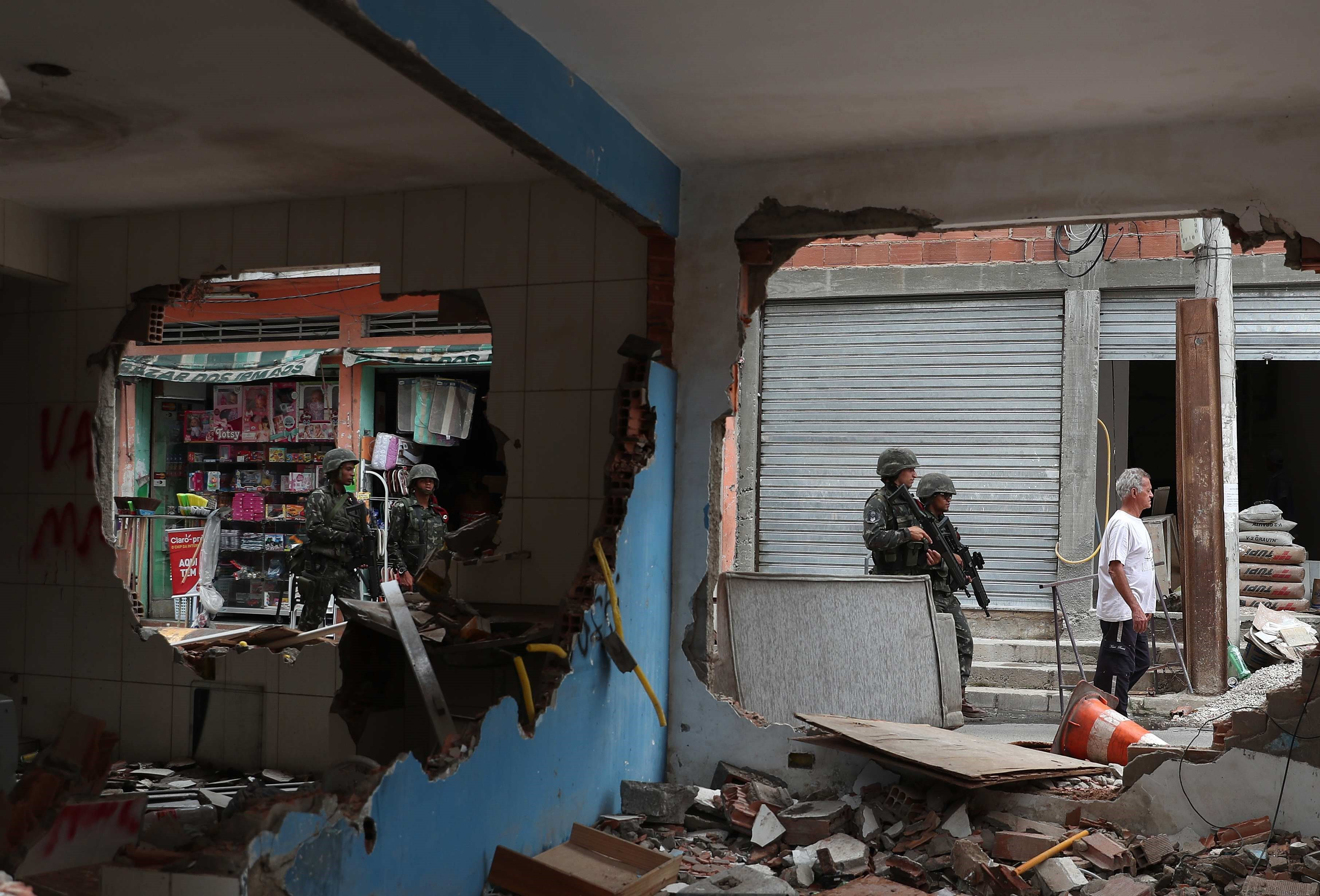 Soldats de l'Exèrcit de Brasil patrullen davant la seu de la UPP (Unitat de Policia Pacificadora), que va ser destruïda per narcotraficants en la favela Ilha do Governado, a Rio de Janeiro (Brasil). /MARCELO SAYAO