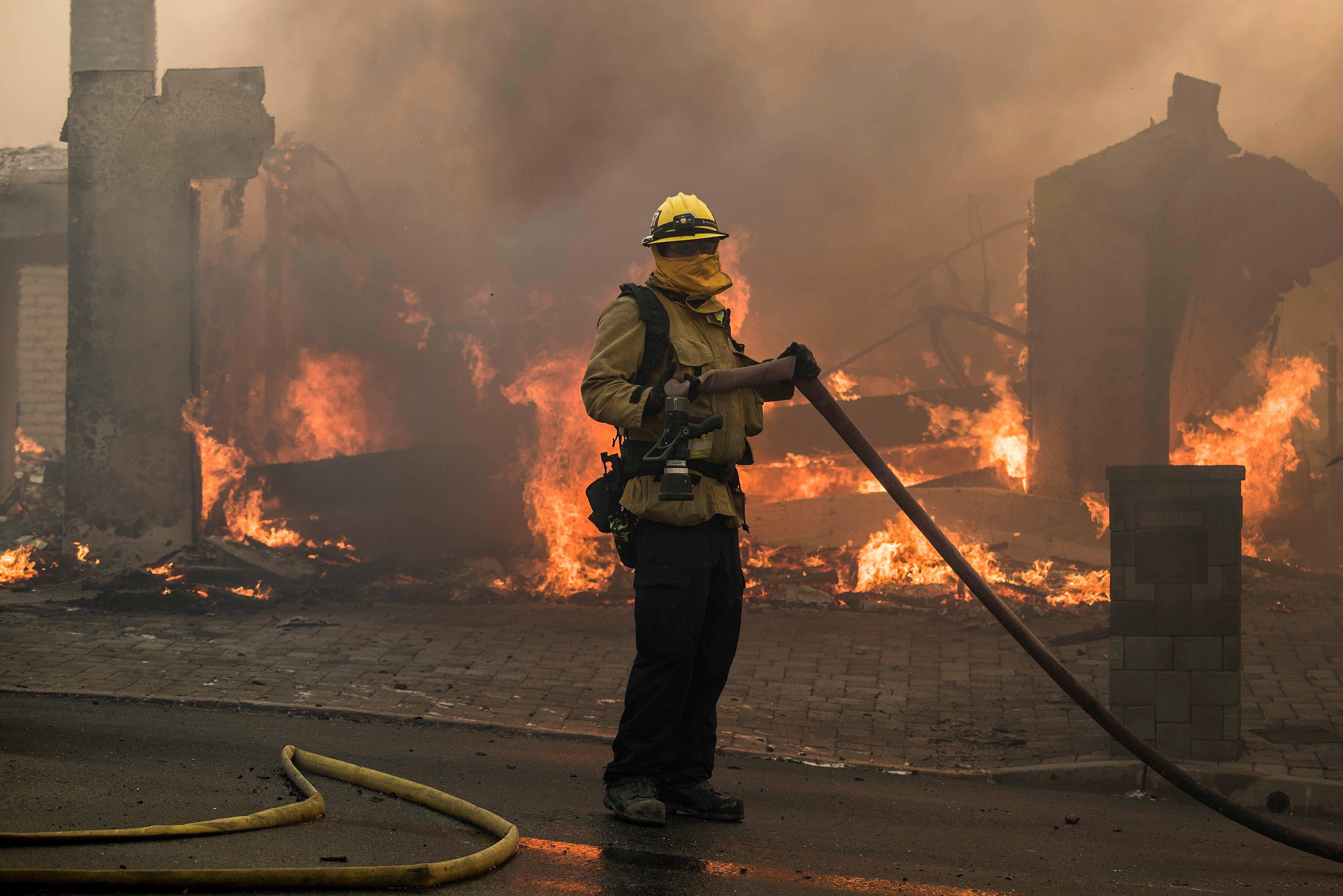Un bomber treballa en les tasques d'extinció d'un incendi a Ventura, Califòrnia (Estats Units). /JOHN CETRINO