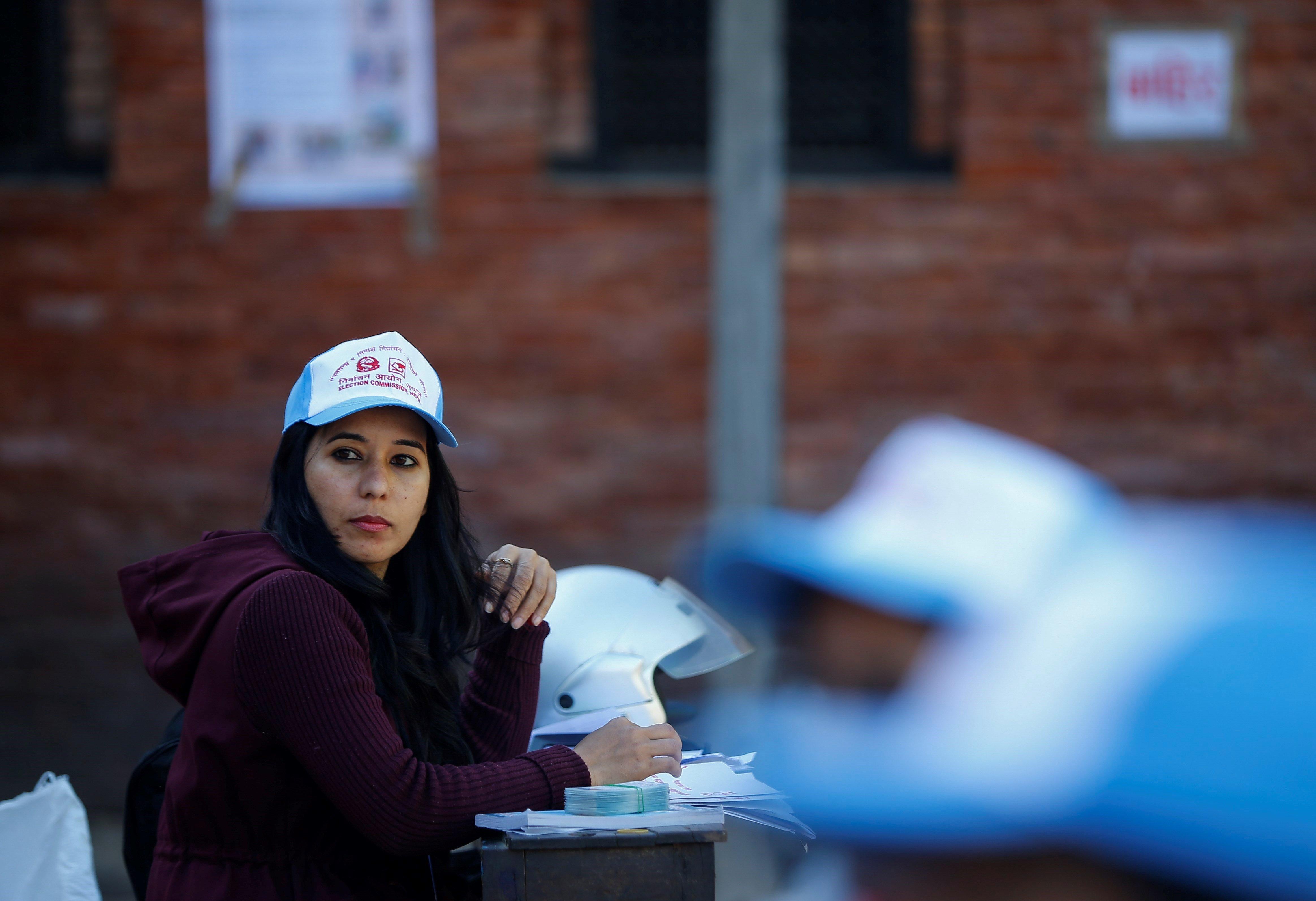 Una empleada electoral distribueix carnets d'identificació de votants la vesprada de les eleccions a Kàtmandu (Nepal). /NARENDRA SHRESTHA