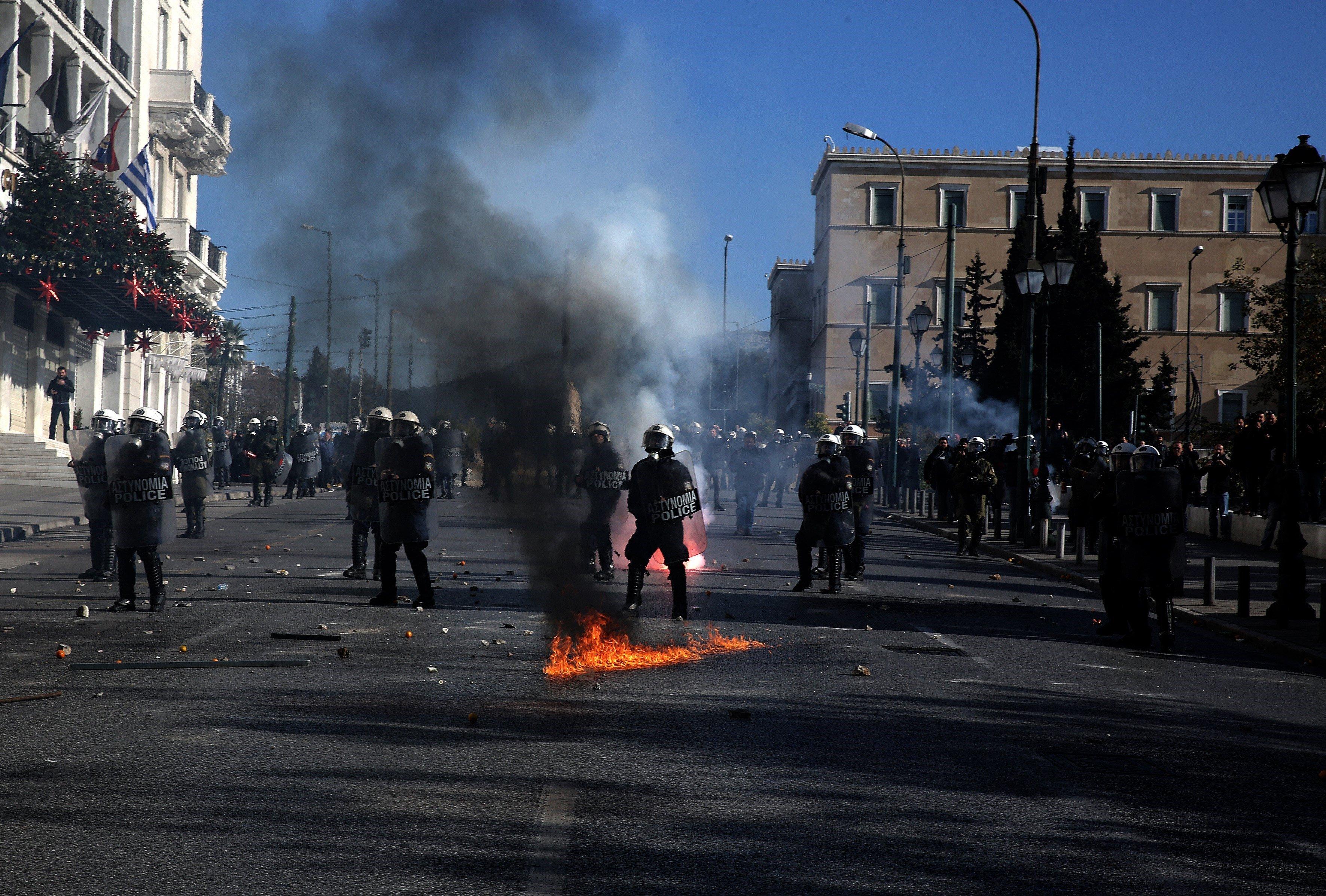 Manifestants llancen còctels molotov contra els antidisturbis durant una protesta amb motiu de l'aniversari de la mort del jove Alexis Grigoropoulos, mort a tirs per un agent el 6 de desembre del 2008, a Atenes (Grècia). /ALEXANDROS VLACHOS