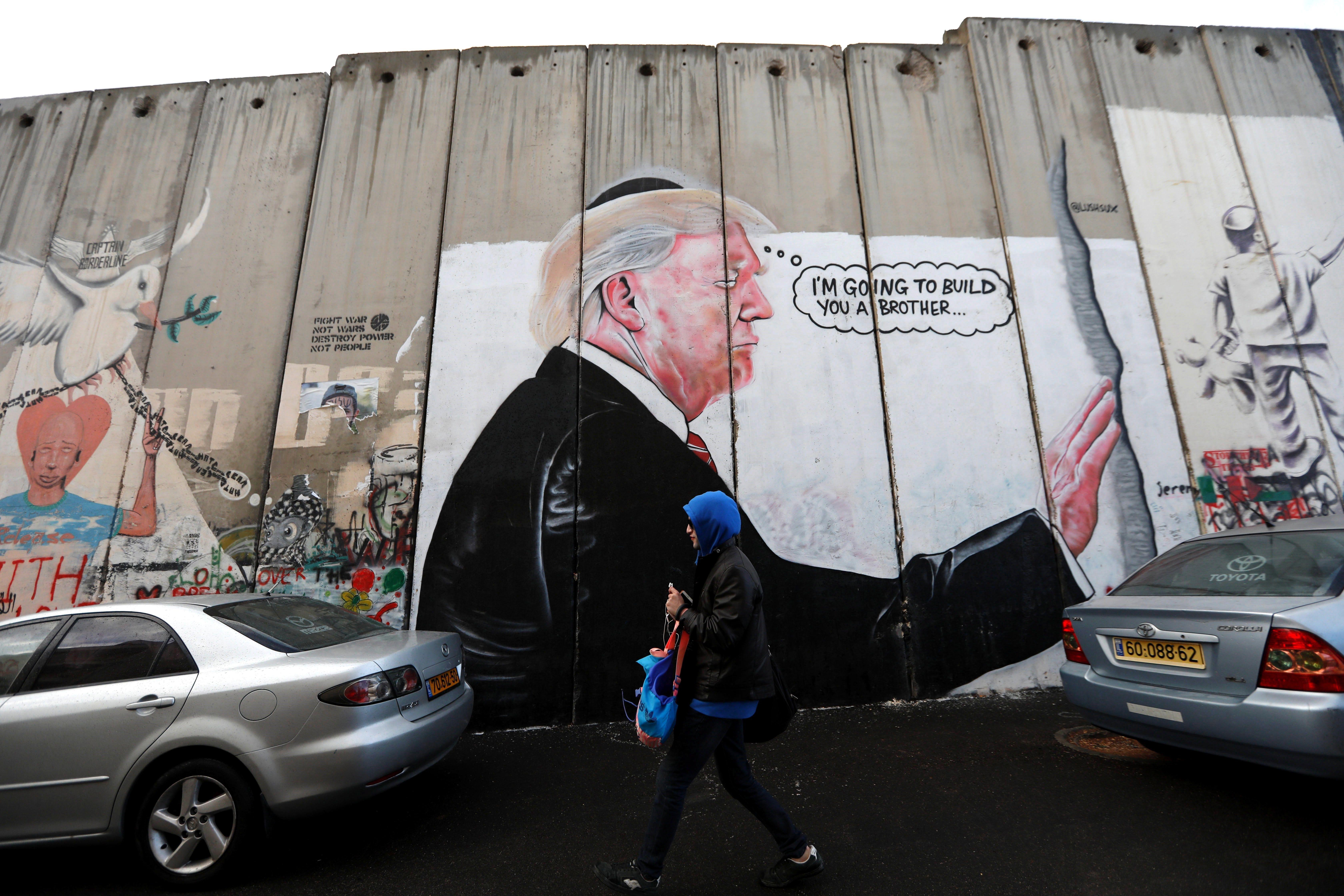 Una dona camina al costat d'un dibuix del president dels EUA, Donald Trump, en el mur de separació israeliana a Cisjordània. /ABED AL HASHLAMOUN
