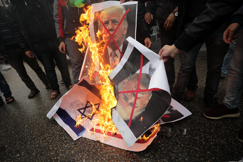 Diversos palestins cremen una bandera nord-americana i d'Israel, i imatges del president dels EUA, Donald Trump, i del primer ministre israelià Benjamin Netanyahu. /MOHAMMED SABER