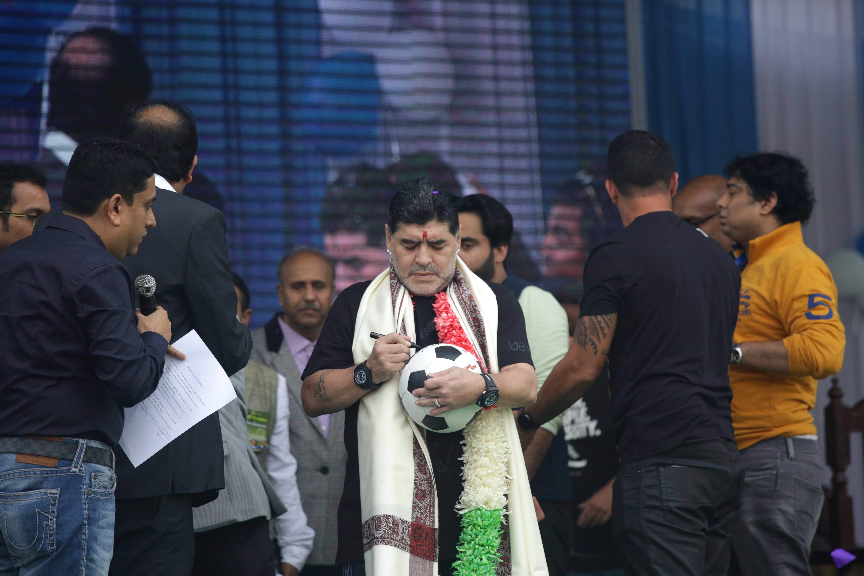 L'exfutbolista argentí Diego Armando Maradona signa un autògraf en una pilota a Calcuta (Índia). /PIYAL ADHIKARY
