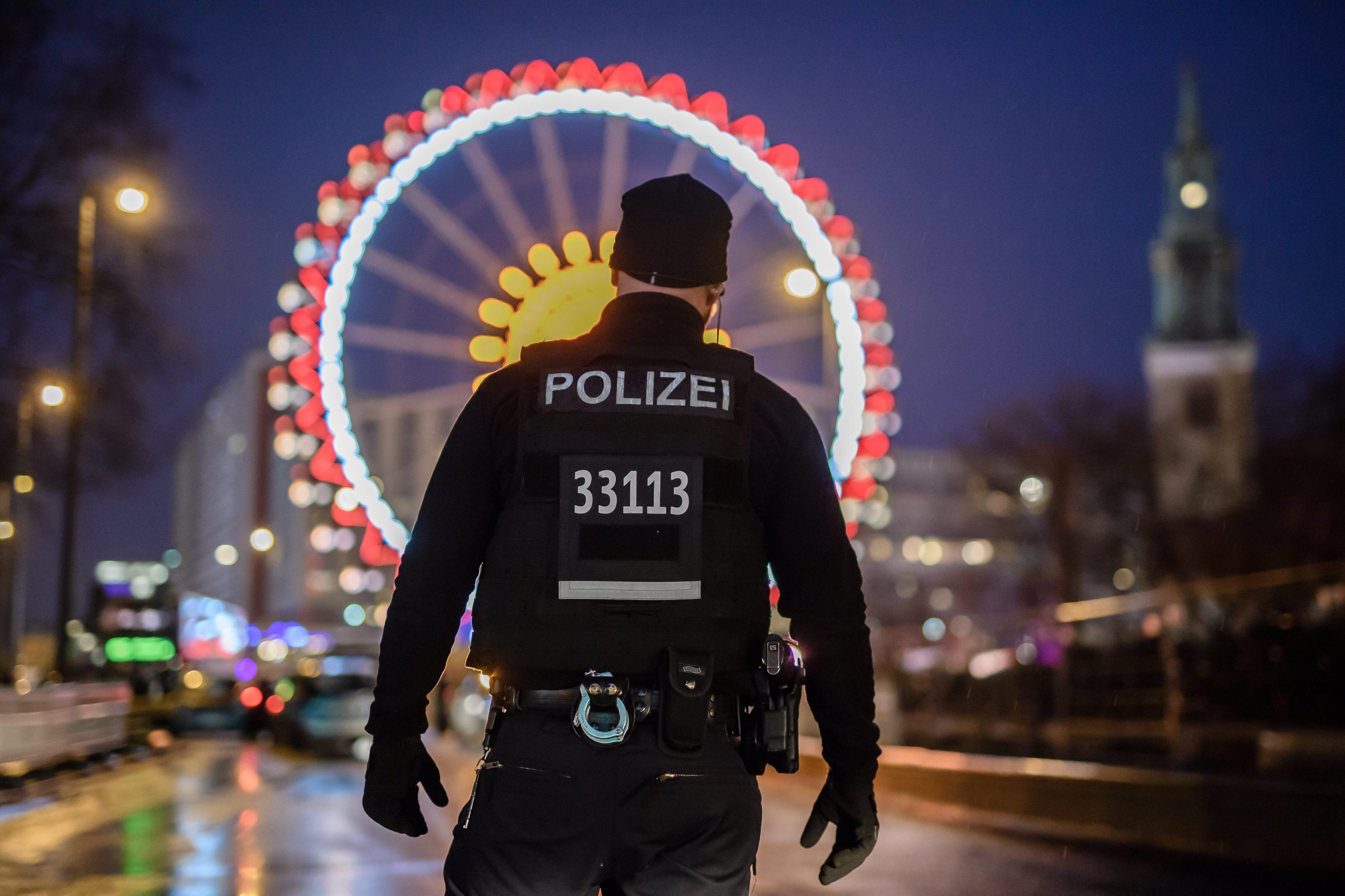 Un agent de policia alemany fa guàrdia davant d'un mercat ambulant nadalenc prop d'on es va produir un accident de trànsit a l'Alexanderplatz de Berlín, Alemanya. /CLEMENS BILAN