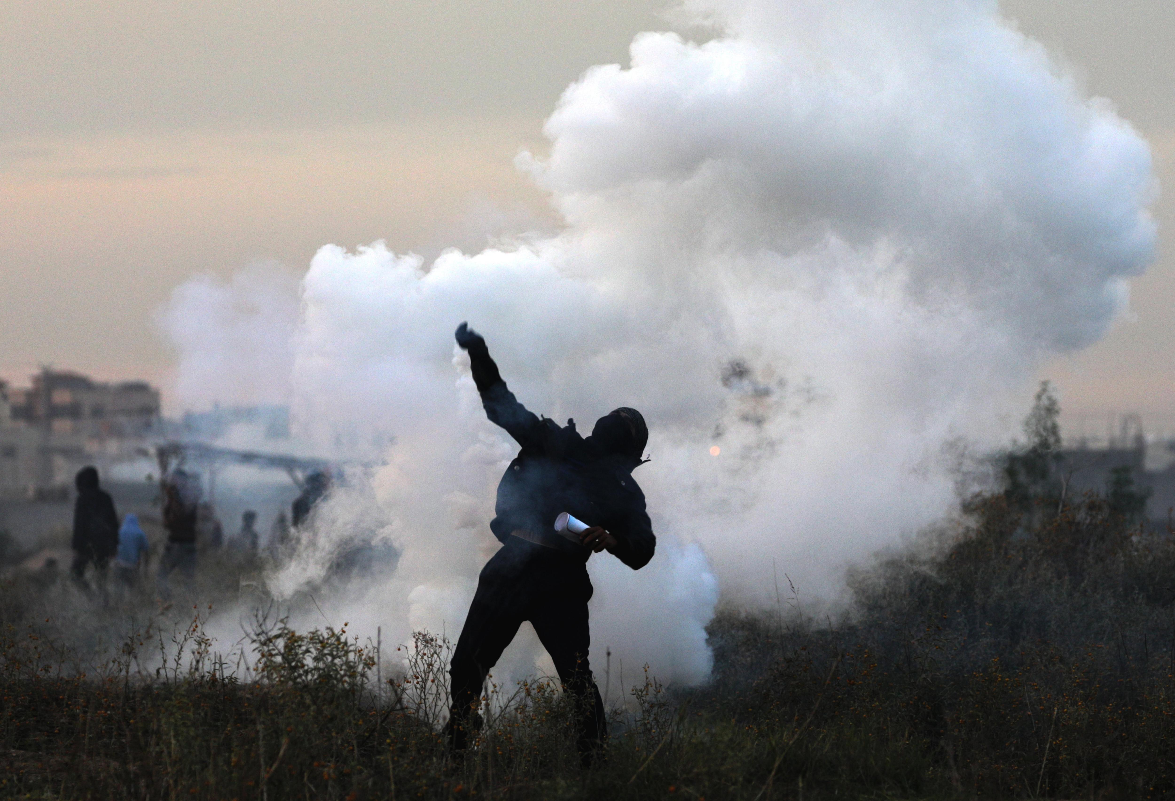 Un manifestant palestí retorna una bomba de gas israelià durant enfrontaments a prop a la frontera amb Israel. /MOHAMMED SABER