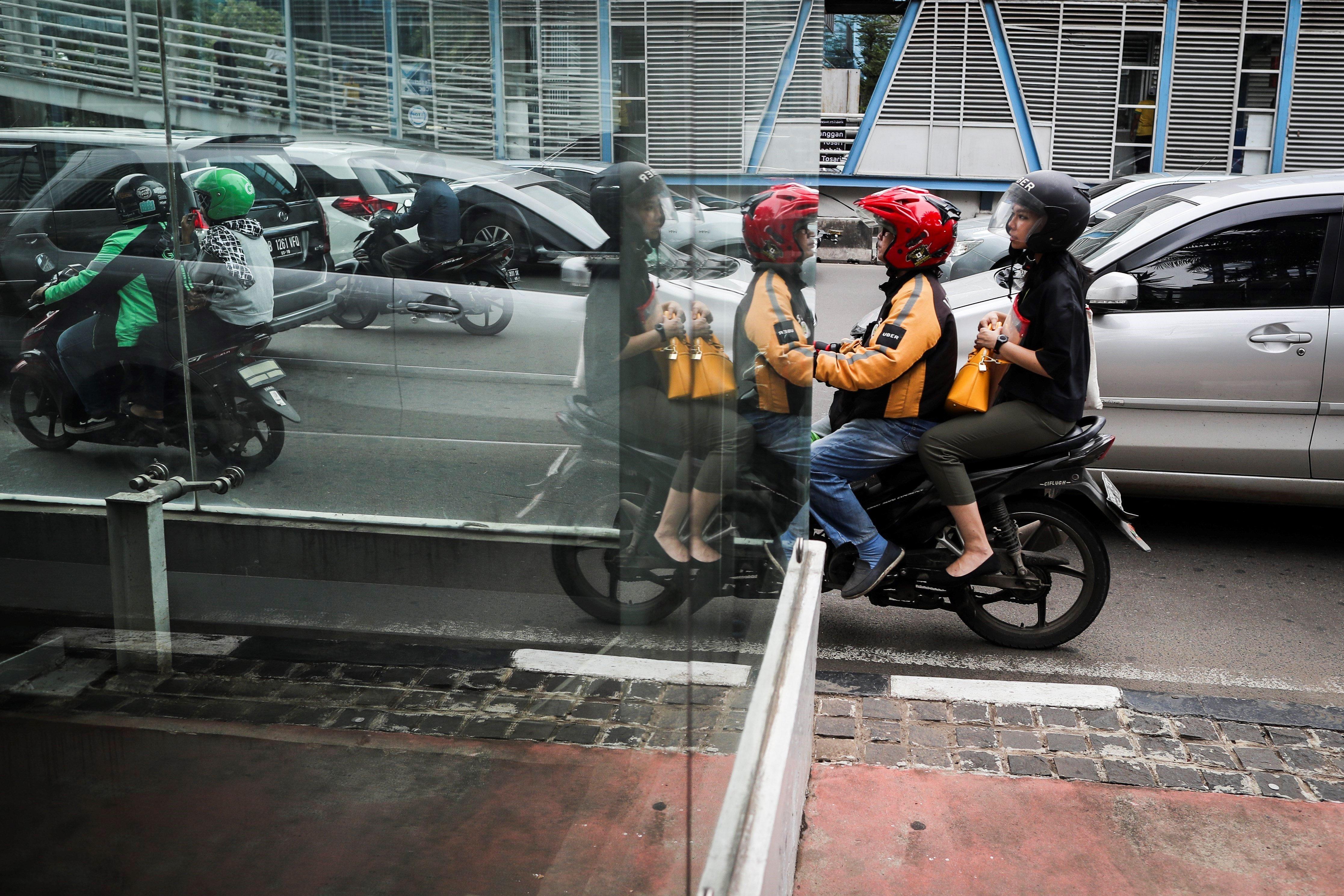 Un conductor de la companyia Uber porta un client amb moto, a Jakarta (Indonèsia). /MAST IRHAM
