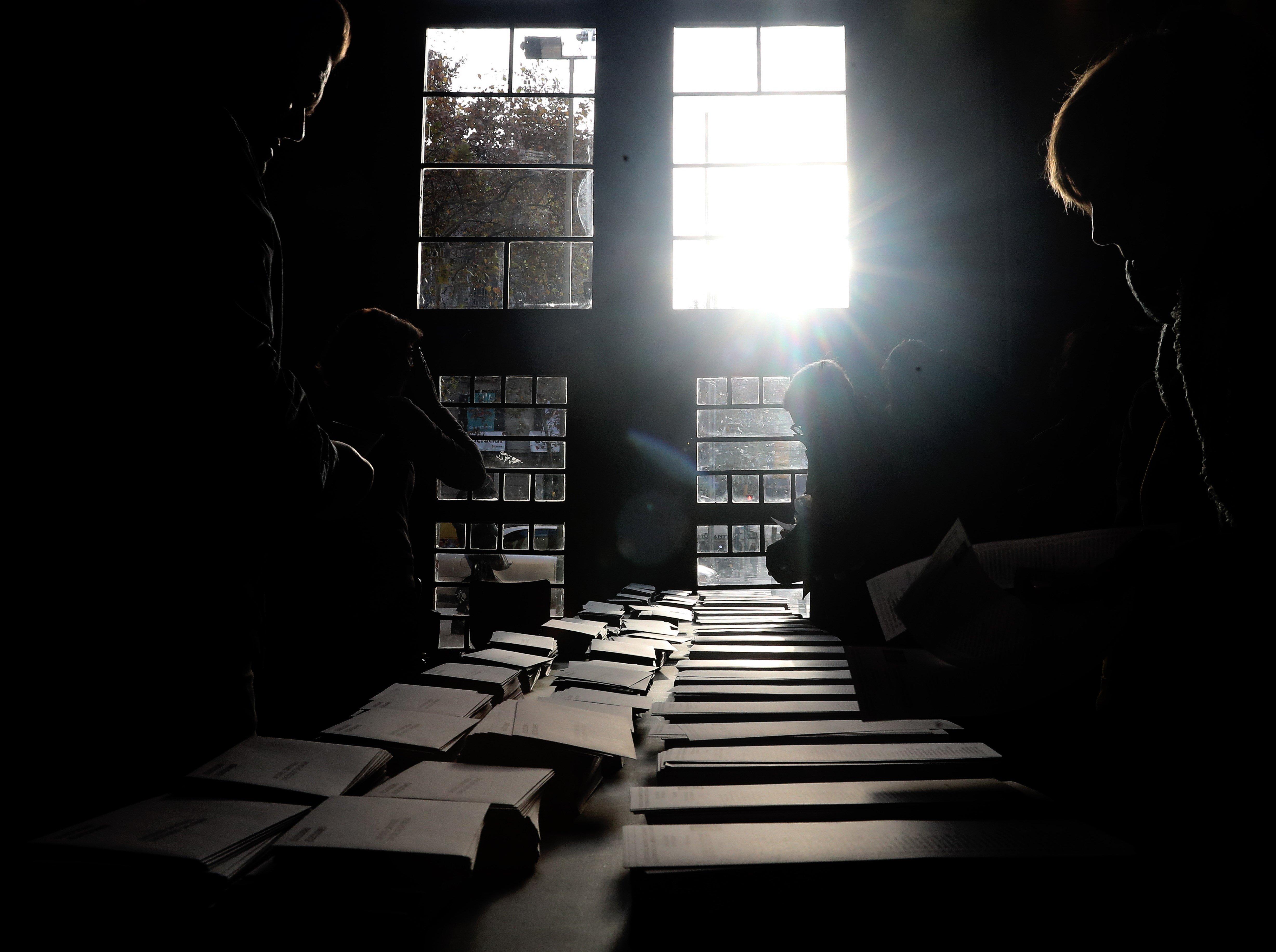 Diversos ciutadans trien les seves paperetes per votar en el col·legi electoral de la plaça de la Universitat. /JAVIER ETXEZARRETA