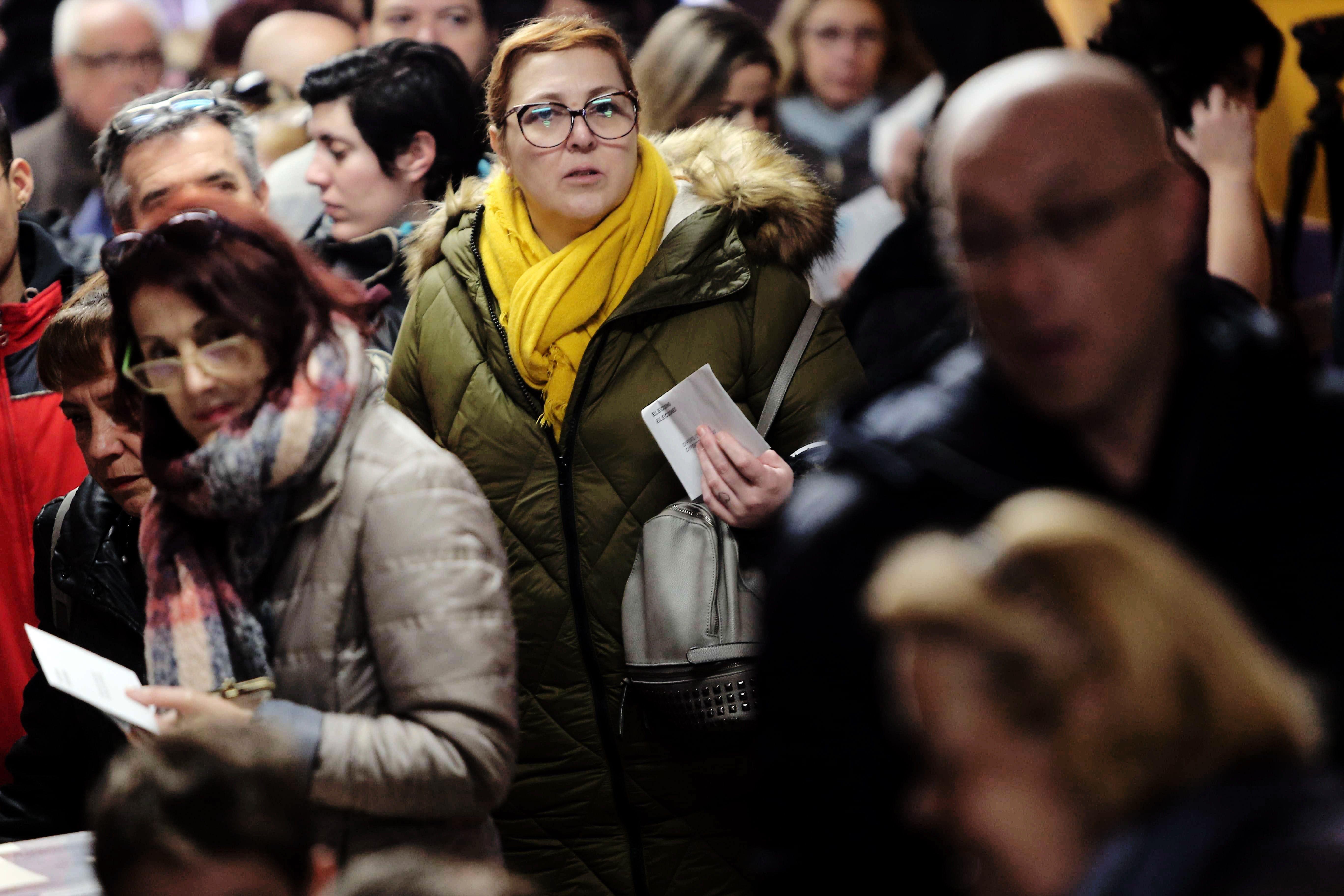 Una dona abrigada amb una bufanda groga espera per dipositar el seu vot en el col·legi electoral Santa Marta de l'Hospitalet de Llobregat. /TONI ALBIR
