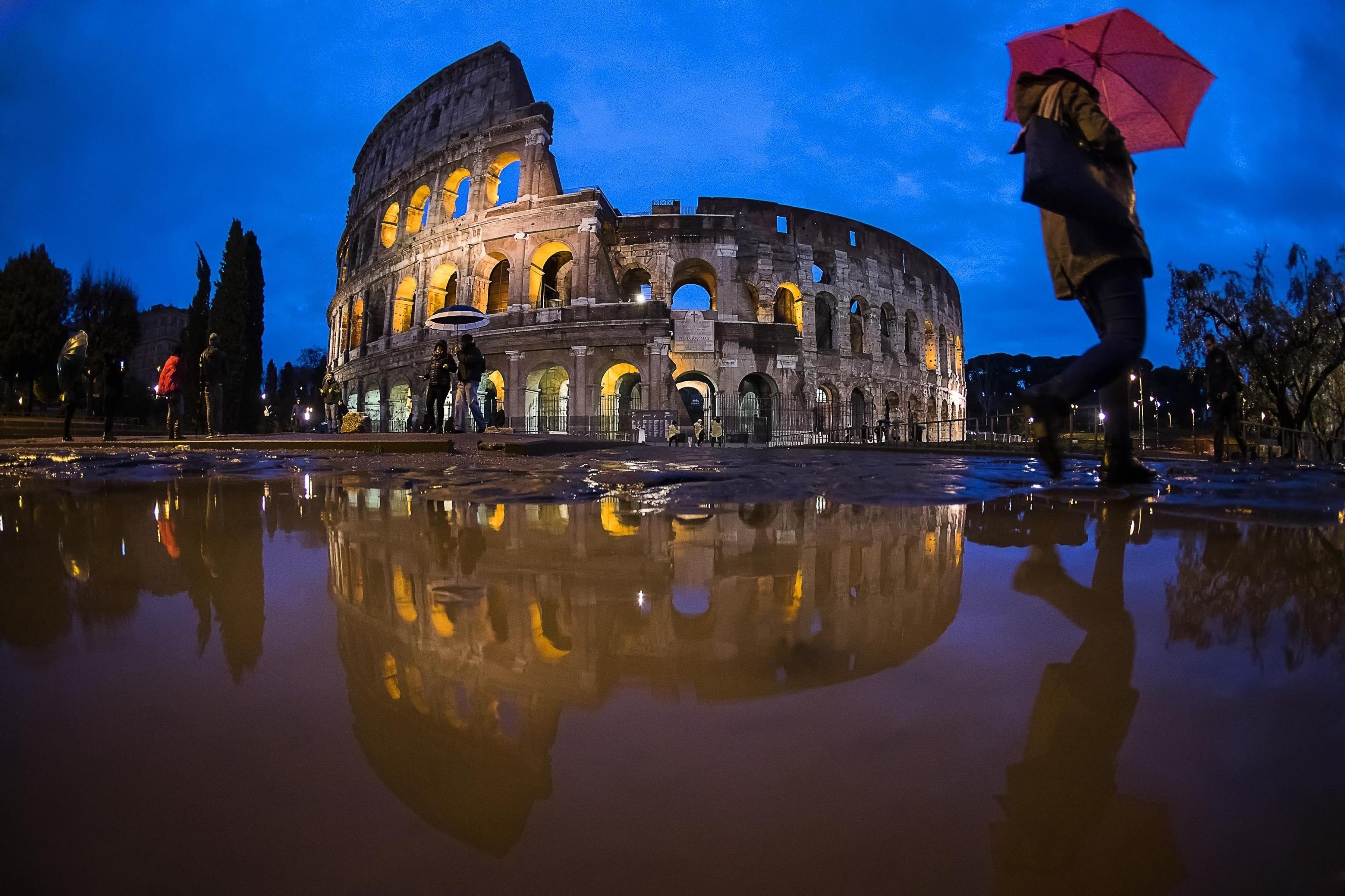 Una turista es protegeix de la pluja amb un paraigua prop del Coliseu de Roma (Itàlia) /ANGELO CARCONI
