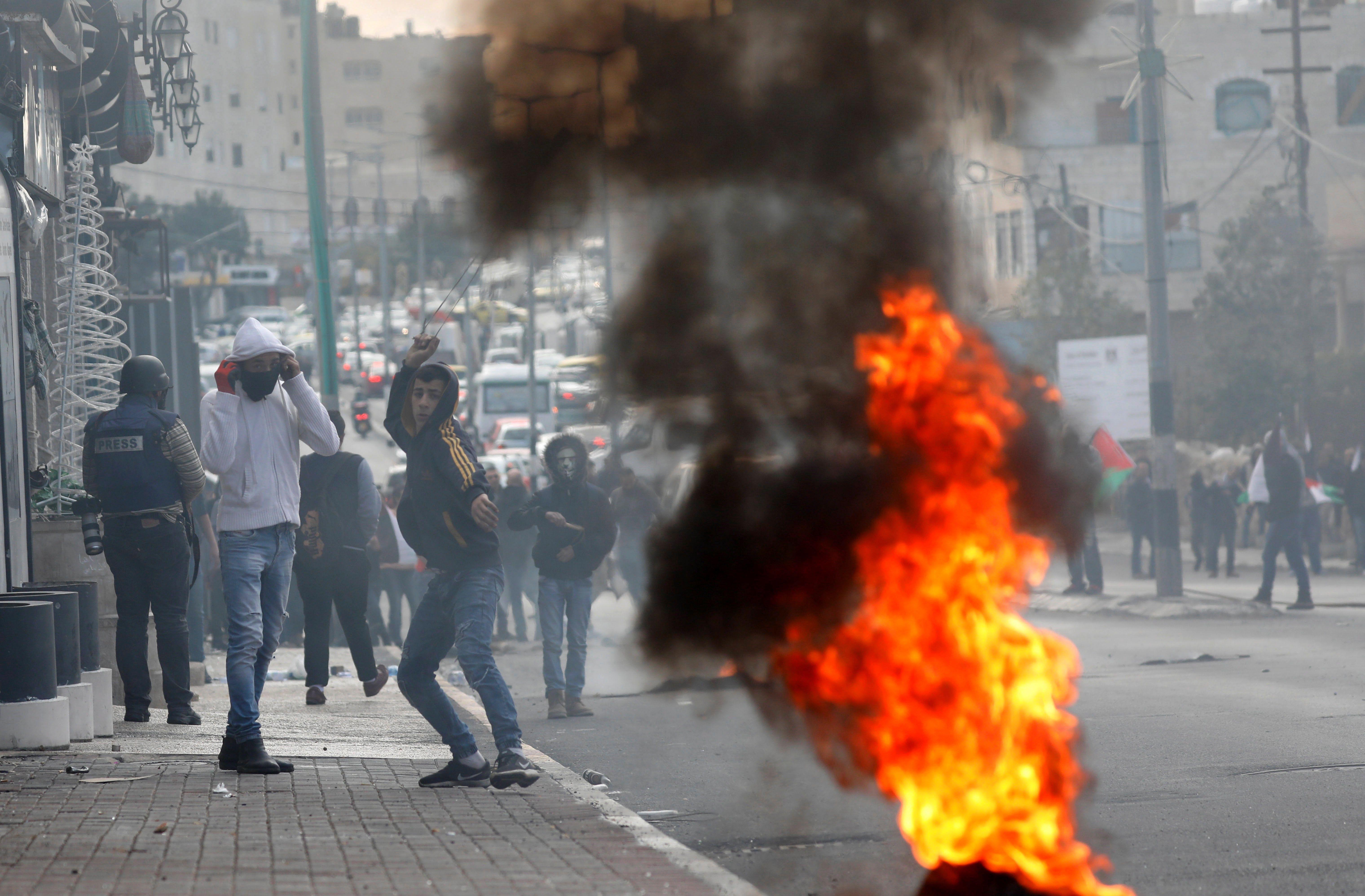 Un palestí llançar pedres contra les tropes israelianes durant una manifestació contra la decisió del president dels EUA, Donald Trump, de reconèixer Jerusalem com la capital d'Israel. /ABED AL HASHLAMOUN
