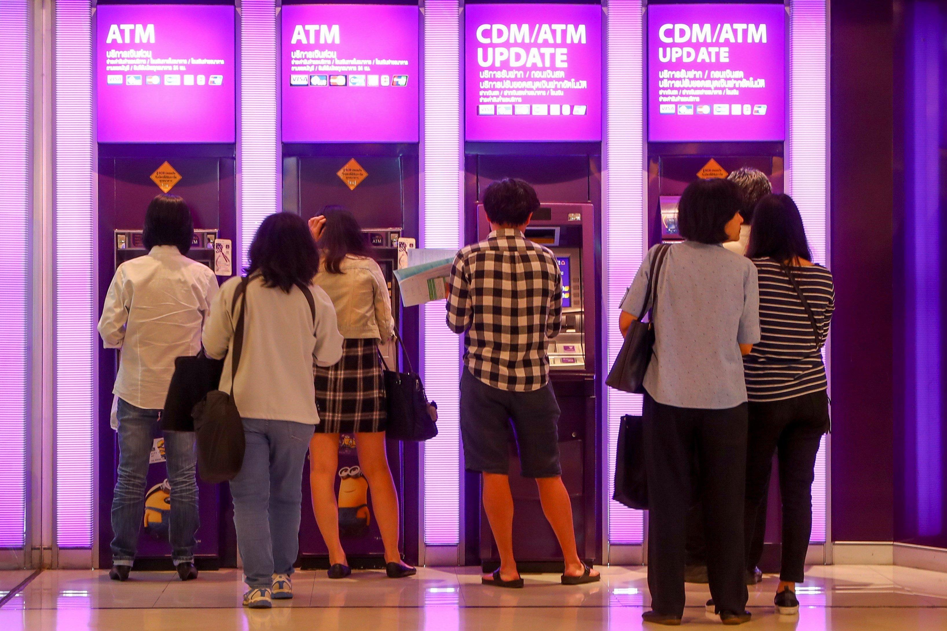 Diverses persones utilitzen caixers automàtics en un banc de Bagkok (Tailàndia). L'economia taliandesa espera assolir el 4% de creixement per a aquest final d'any. / DIEGO AZUBEL