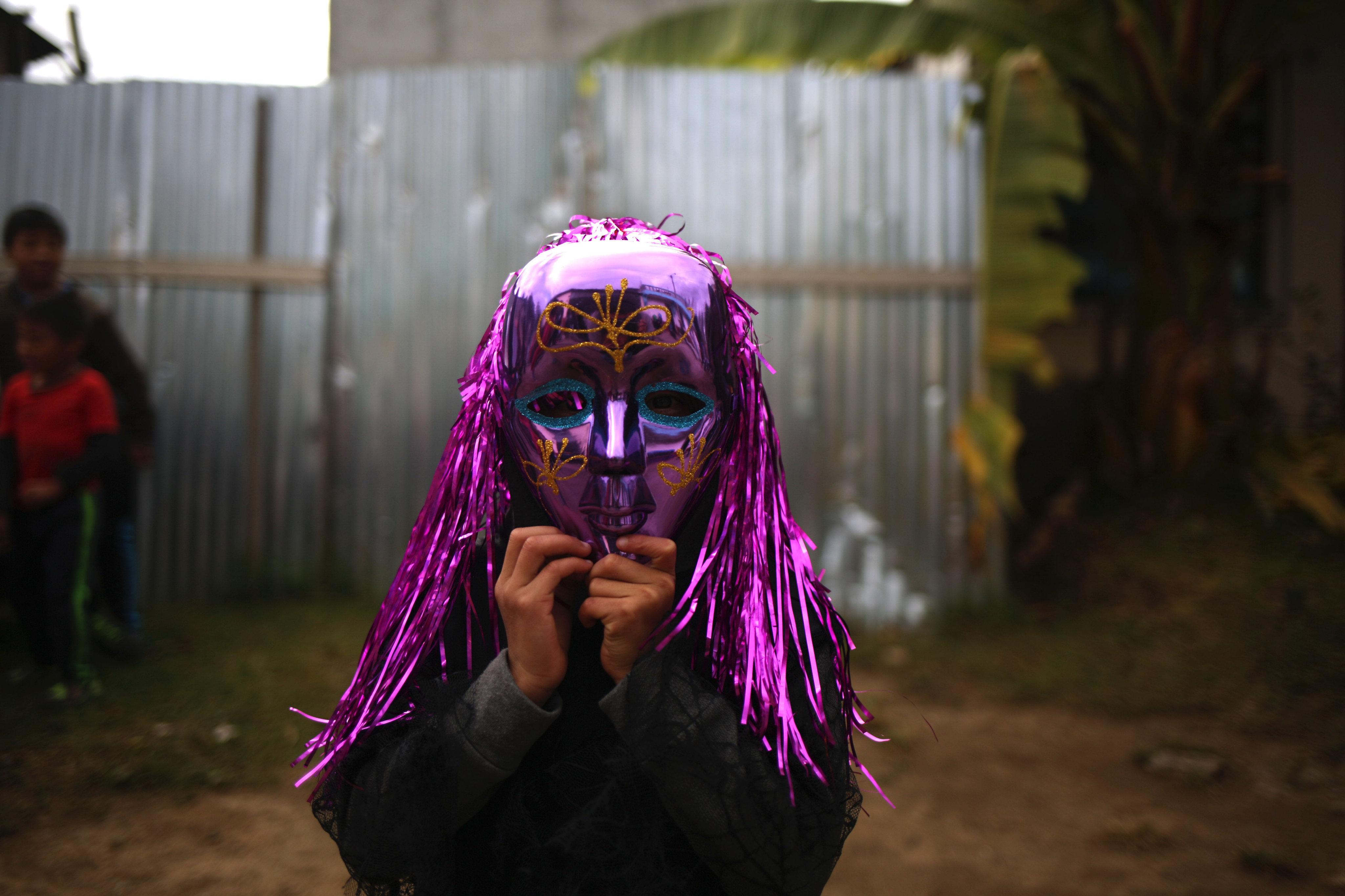 """Una nena sosté una màscara de carnestoltes a la tradició guatemalenca del Convit, celebració que commemora la creació de la """"Comunitat 29 de desembre """"a Saragossa, Chimaltenango. / ESTEBAN BIBA"""