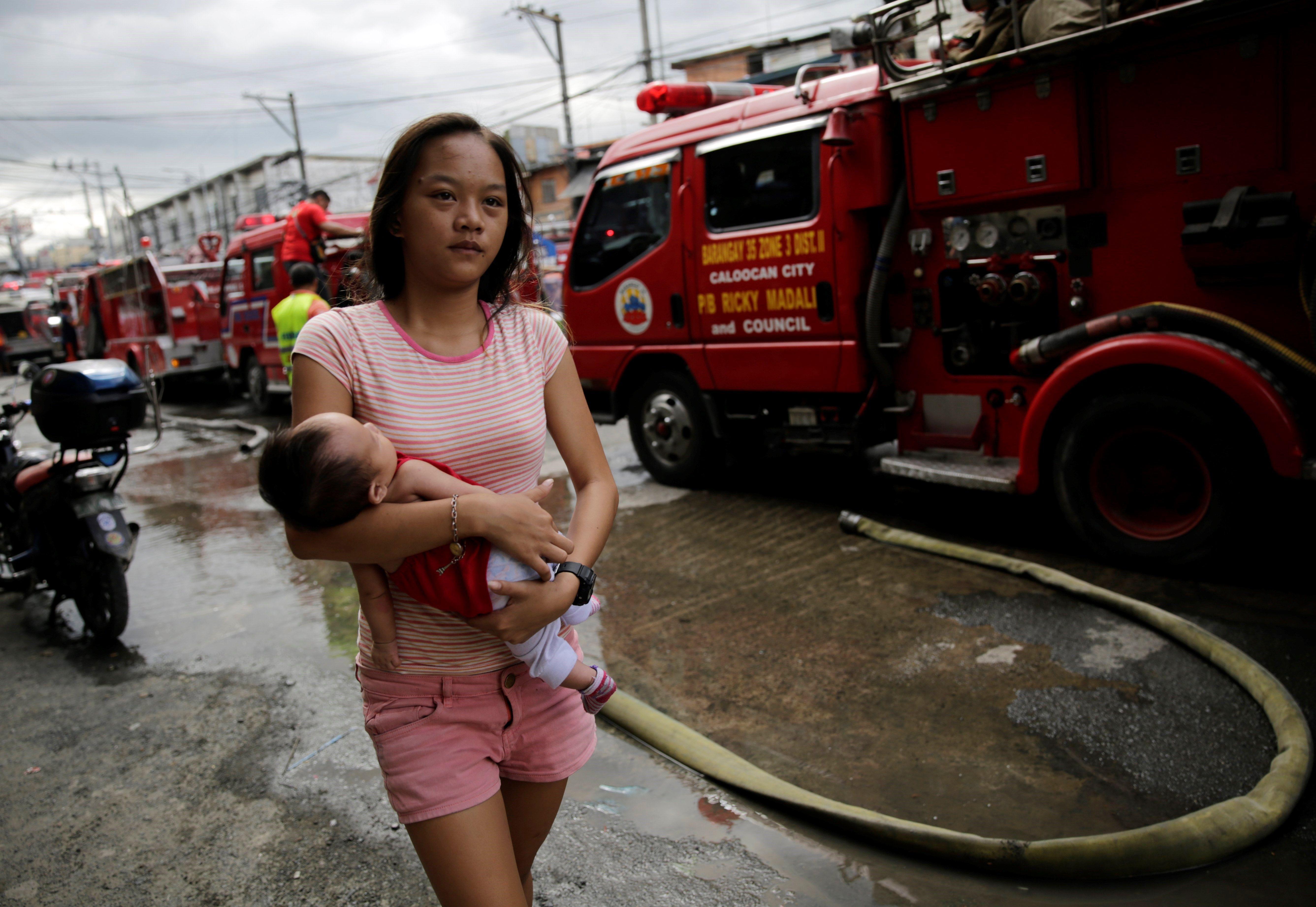 Una dona porta en braços el seu bebè a la zona d'un incendi de l'àrea residencial de Manila (Filipines) on s'han cremat almanco 100 habitatges. / FRANCIS R. MALASIG