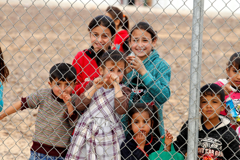 Diversos nins refugiats sirians rere una reixa d'un camp de refugiats a Azraq, Jordània. /AHMAD ABDO